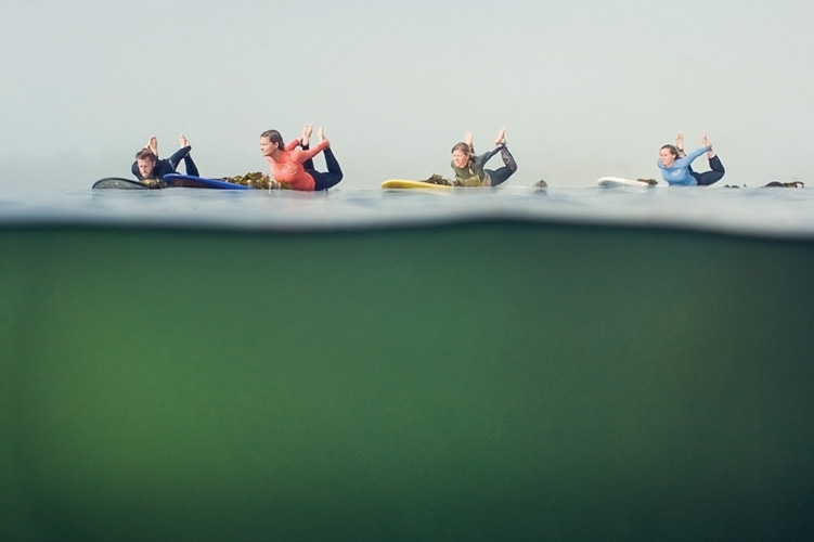 Group of friends practicing yoga on SUP's in Tofino