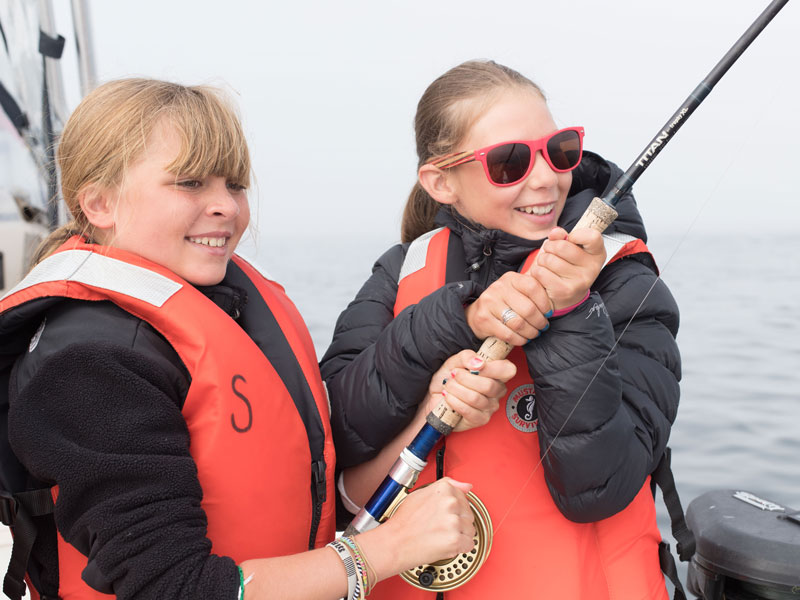 Girls stoked with a fish on their line in Tofino, BC.