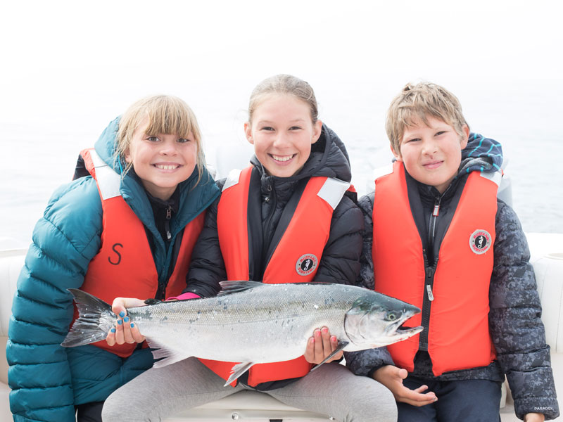 Kids holding a salmon on a family fishing trip off the Tofino coast