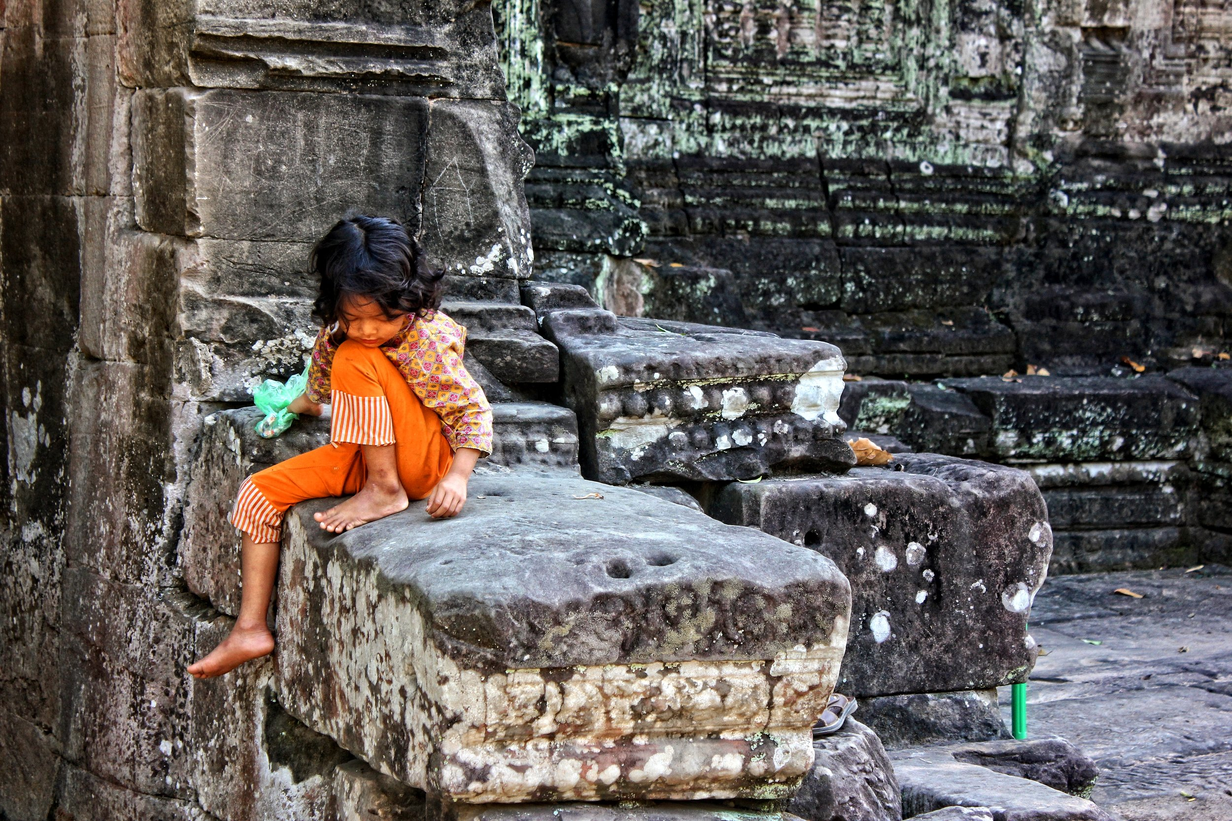 A girl waits to ask for money as travelers pass by her at Angkor Wat.