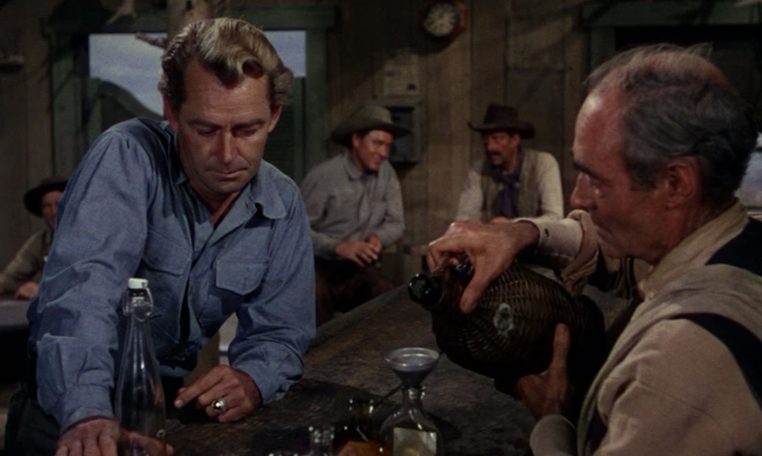 Bartender Will Atkey (John Miller) filling whiskey bottles from a jug.