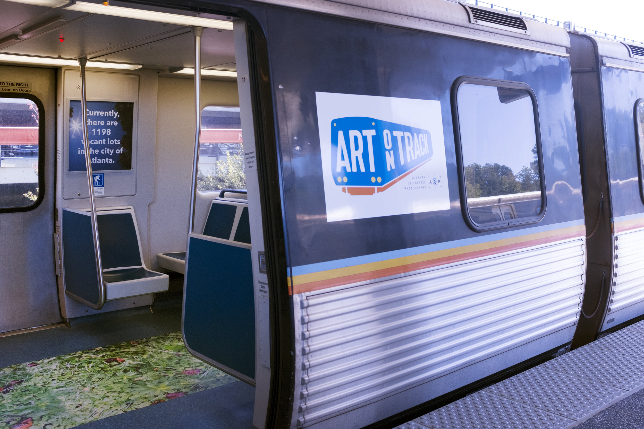 "Exterior of MARTA car featuring ACP's ""Art on Track"" informational panel."