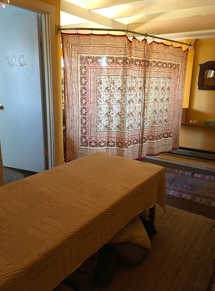 Massage room, changing area, and doorway to bathroom