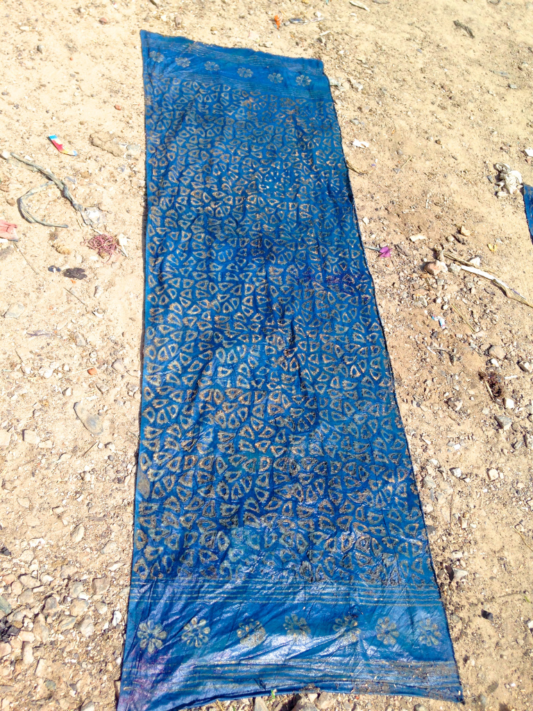 My mud resist woodblock printed fabric after a second dip into the indigo vat. Drying and oxygenating on the streets of Bagru