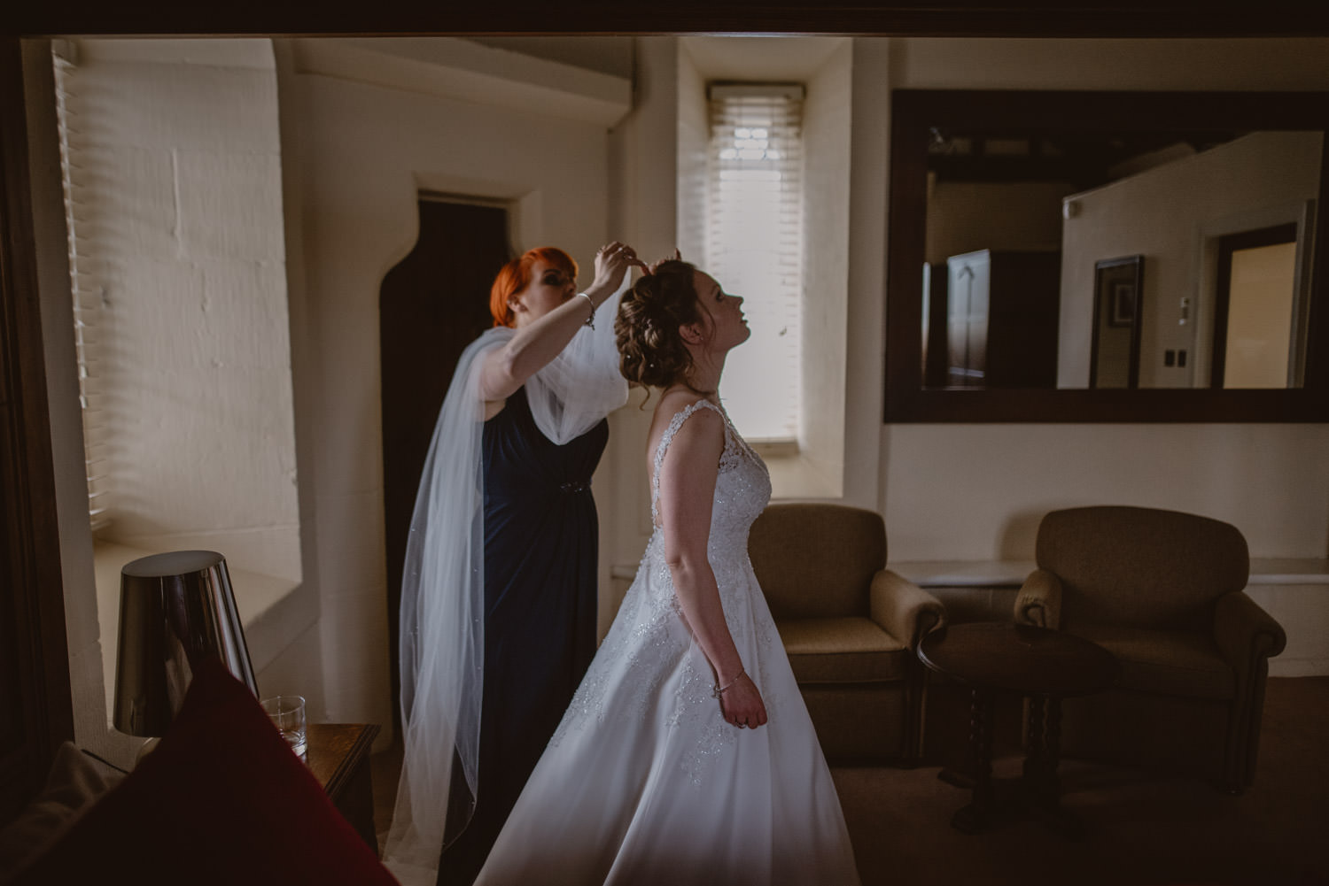 Bridesmaid putting the veil on the bride for her wedding in Peckforton Castle