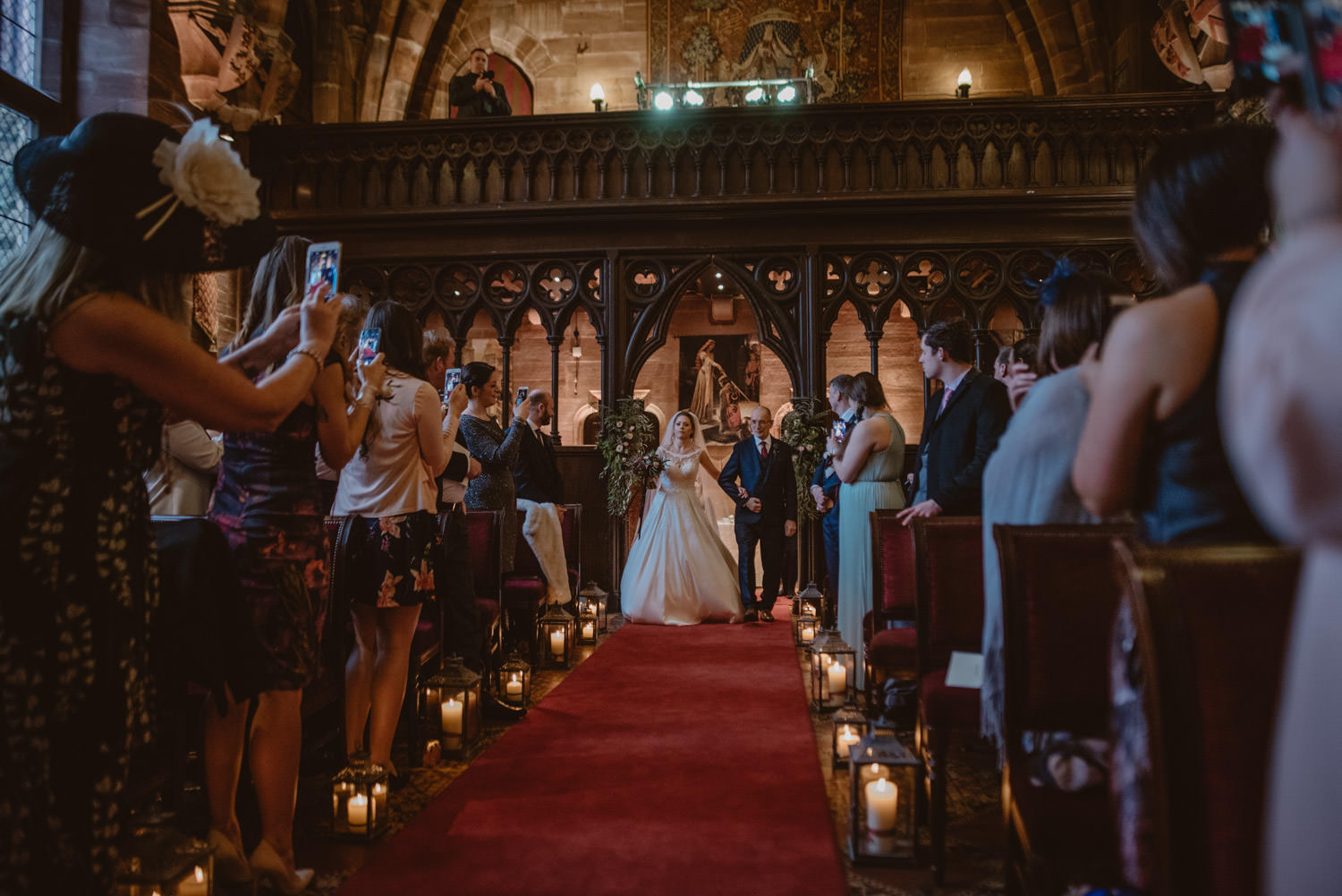 Bride and her father walking the aisle in Peckforton Castle