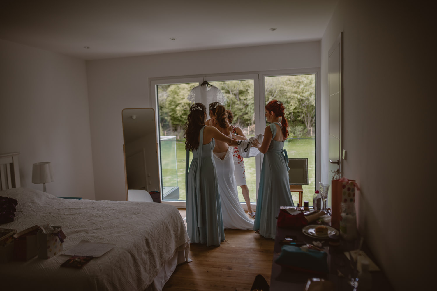 bridesmaids helping the bride with the wedding dress