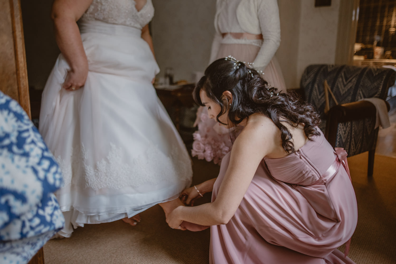 Bridesmaid helping with the wedding shoes