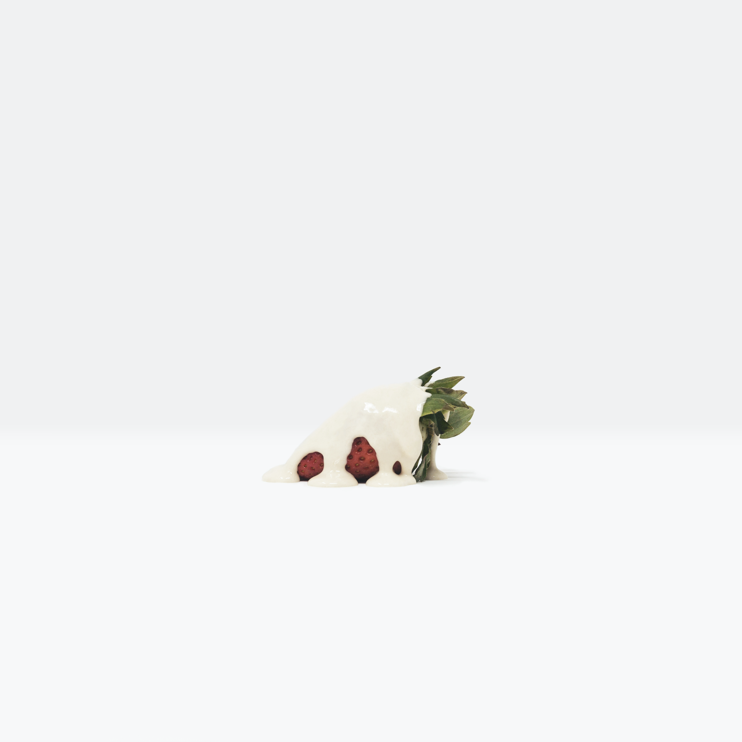 Minimalist, still life photograph of a strawberry covered in a paint-like substance highlighting the value of food, evoking the crucial reflection of the Global Food Crisis