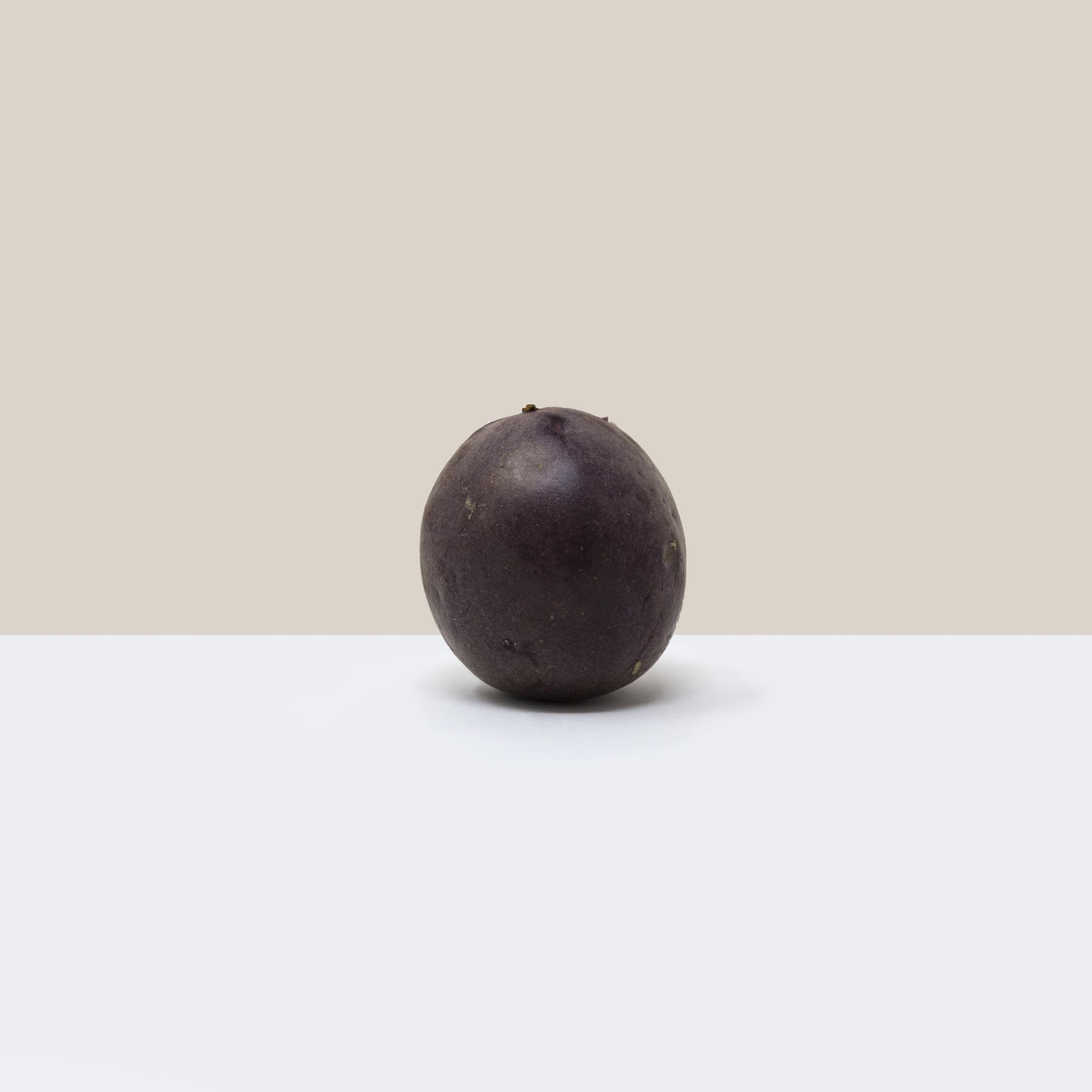 A simple, minimalist, contemporary, fine art photograph of a passionfruit
