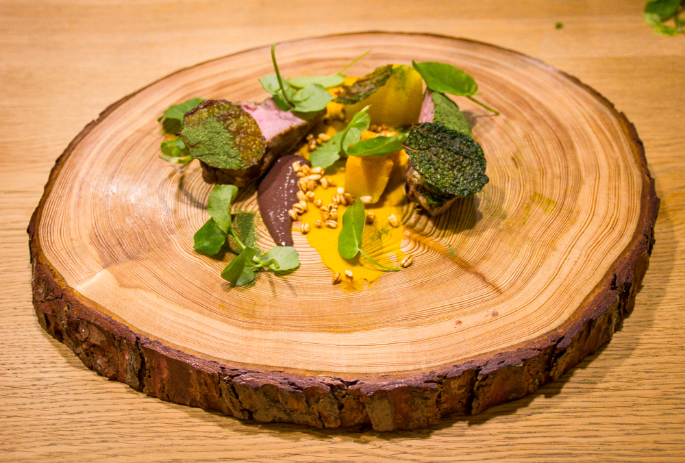 Roast lamb, pumpkin, peat, sloes and wild herbs on a homemade pine plate