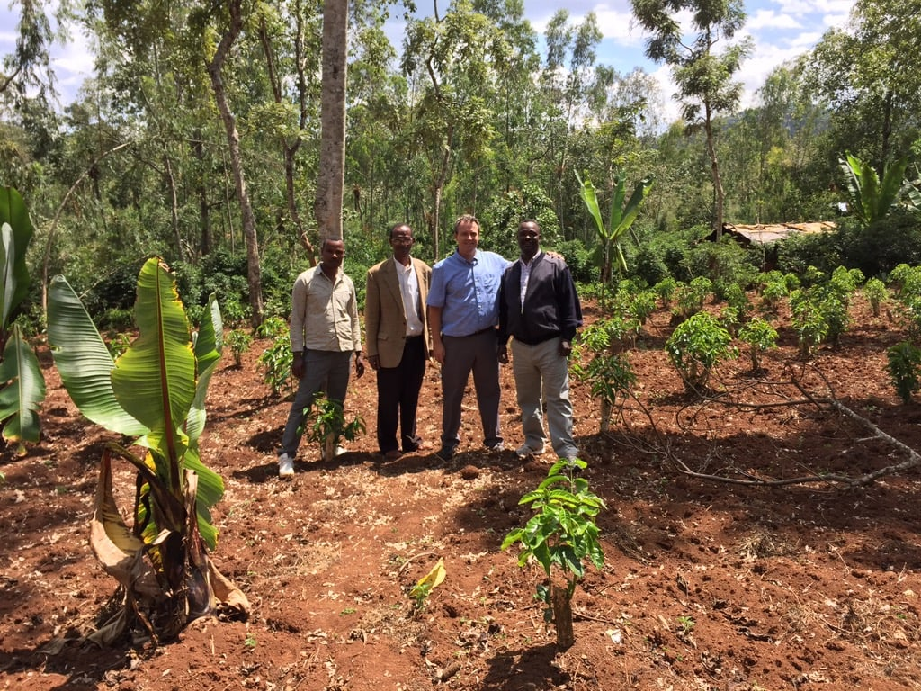 Global CRoss Director Jeff Risk standing in a coffee field with farmers.