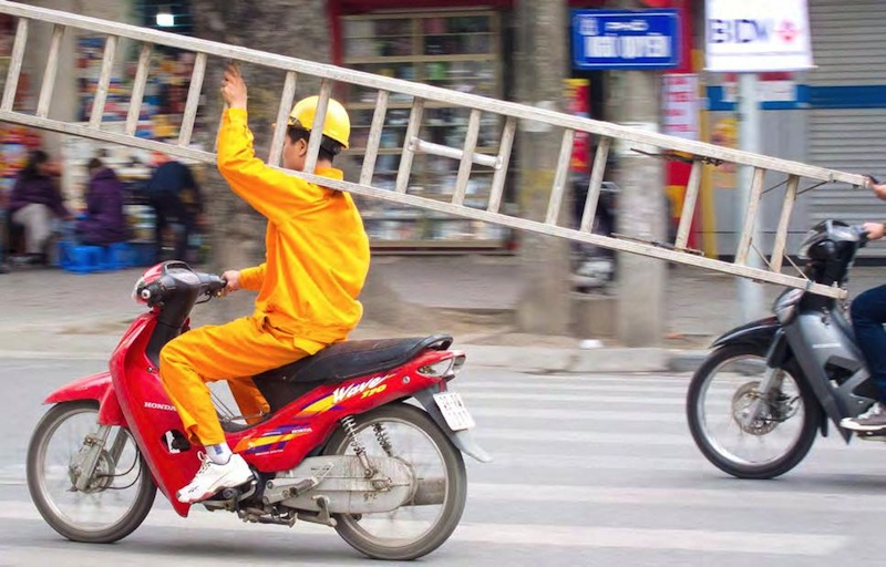 """By placing the subject in such a way that they seem to be moving """"out"""" of the photo, you get a dynamic feeling of speed. In this shot it adds to the sense of recklessness of this motorcyclist with his dangerous load."""