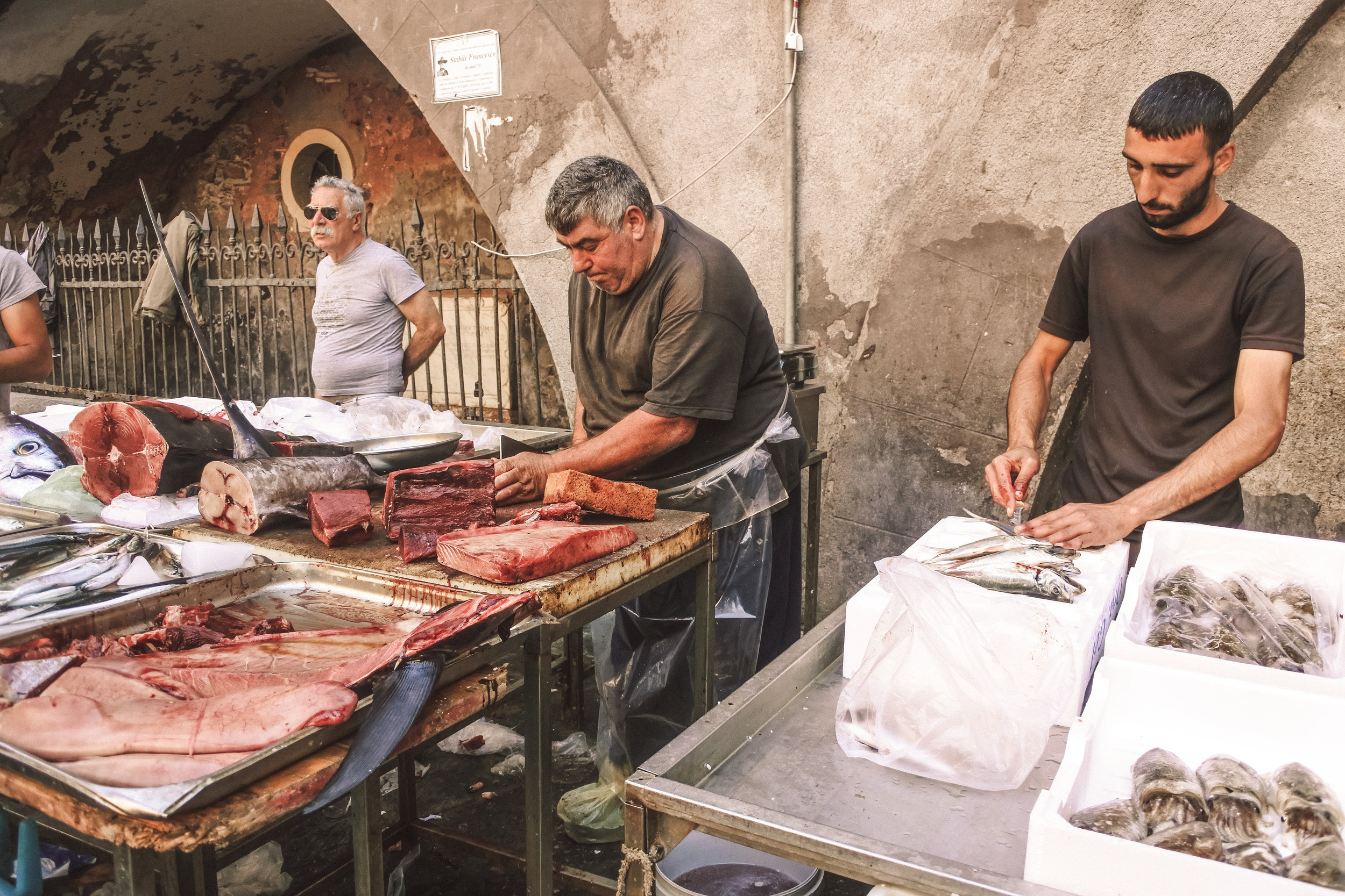 Fish mongers and their catches of the day at La Pescheria in Catania, Italy