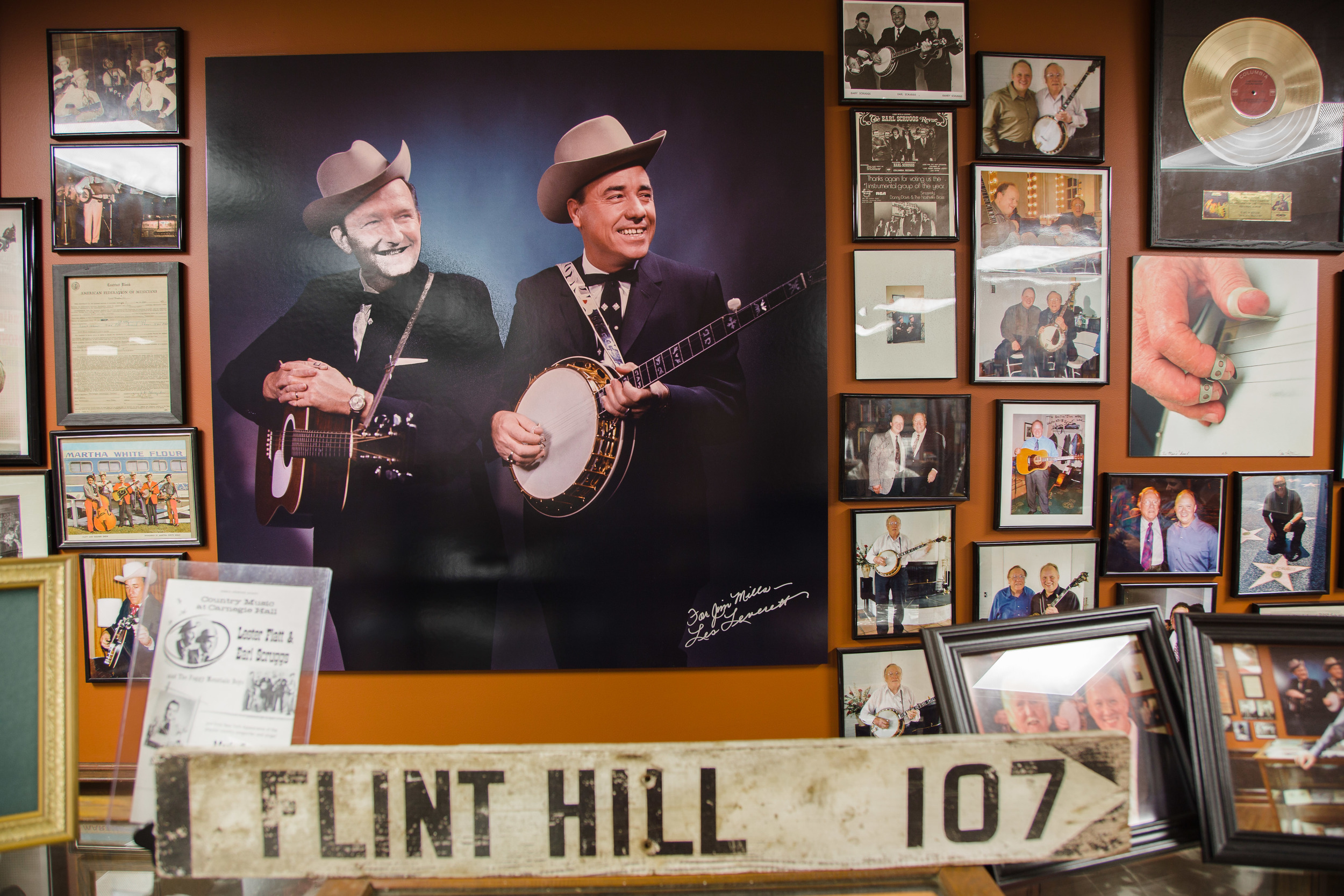 The centerpiece of Mills memorabilia collection is a portrait of Lester Flatt and Earl Scruggs by Nashville photographer Les Leverett, tucked behind a Flint Hill sign from the town in which Scruggs was raised.