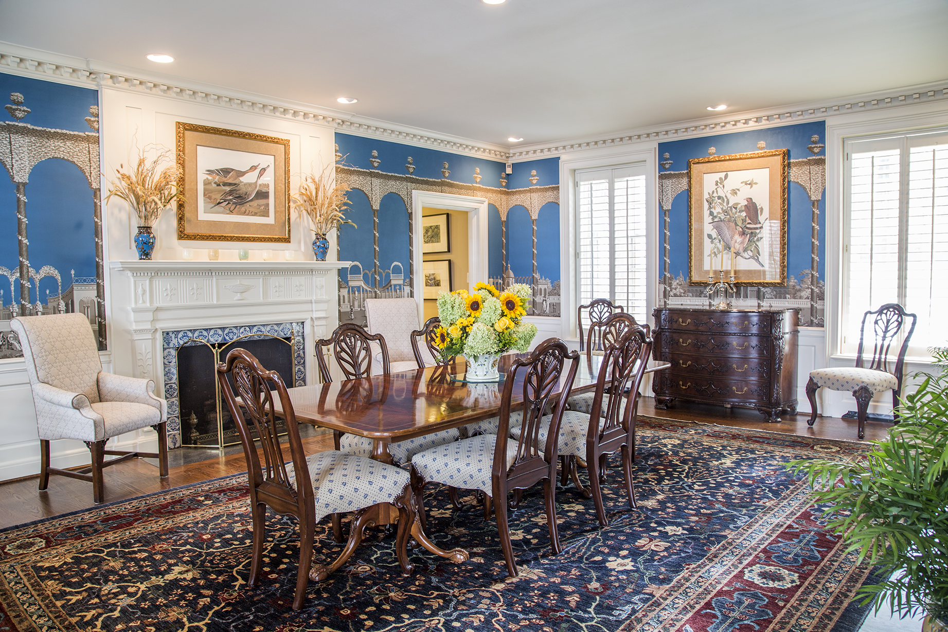 Much of the dining room is original including the wallpaper with its silk-screened scenes that contrast the bright cobalt chalked background. Dusky Duck (1859), a Chromolithograph by American naturalist John James Audubon, sits above the original blue tile framed fireplace.