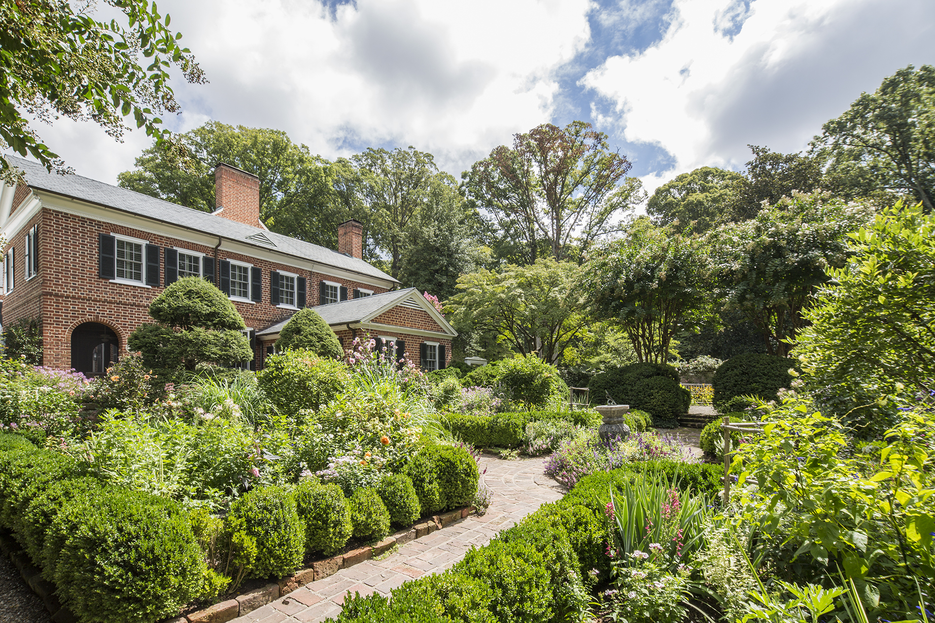 Signature statements of landscape architect Ellen Biddle Shipman's style pepper the garden including:a Chippendale gate, dovecote, garden furniture, and privacy walls that don't compromise the natural setting.