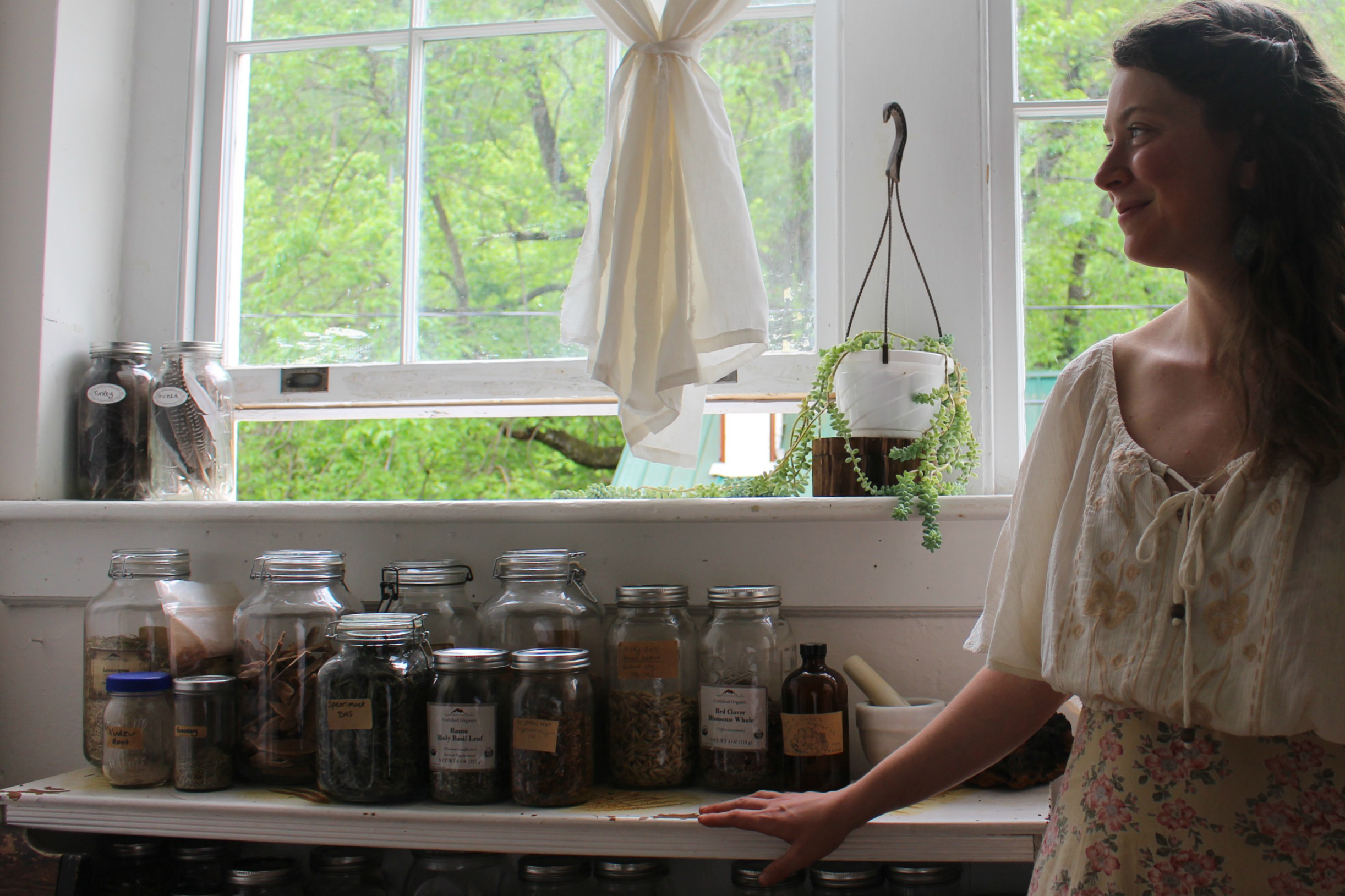 Asia Suler stands beside a stock of dried herbs