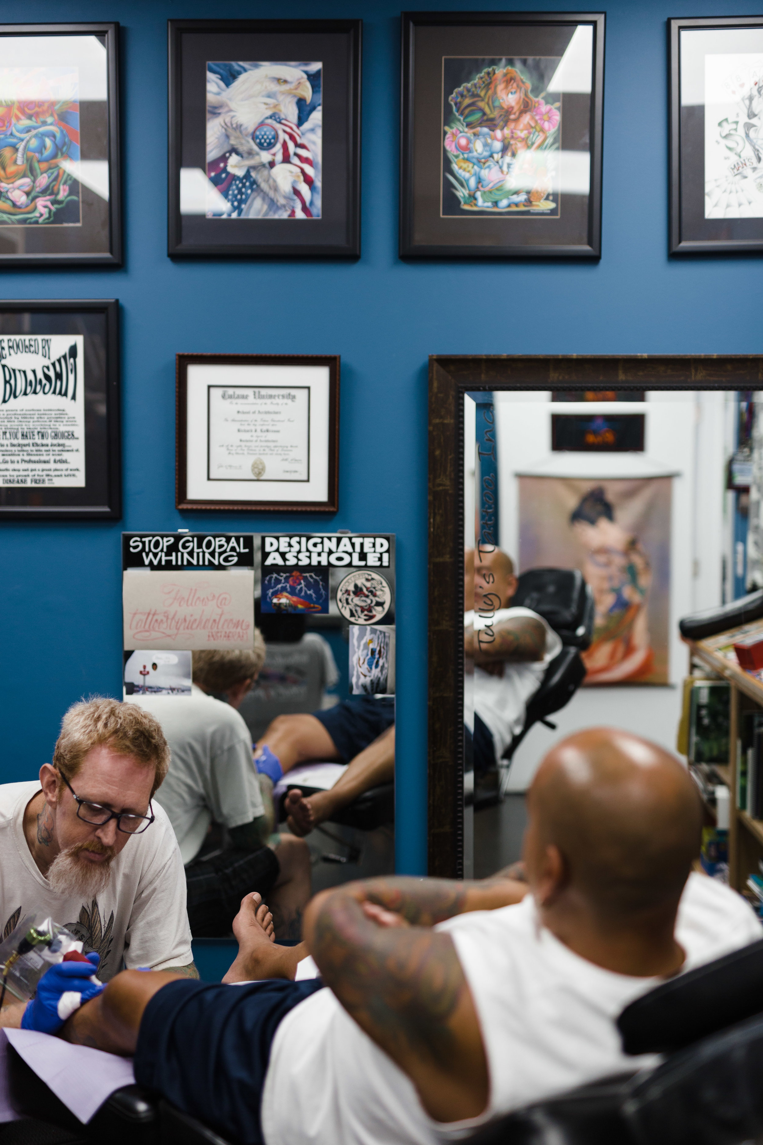 Rich tattoos in his workspace with his Tulane diploma hanging above