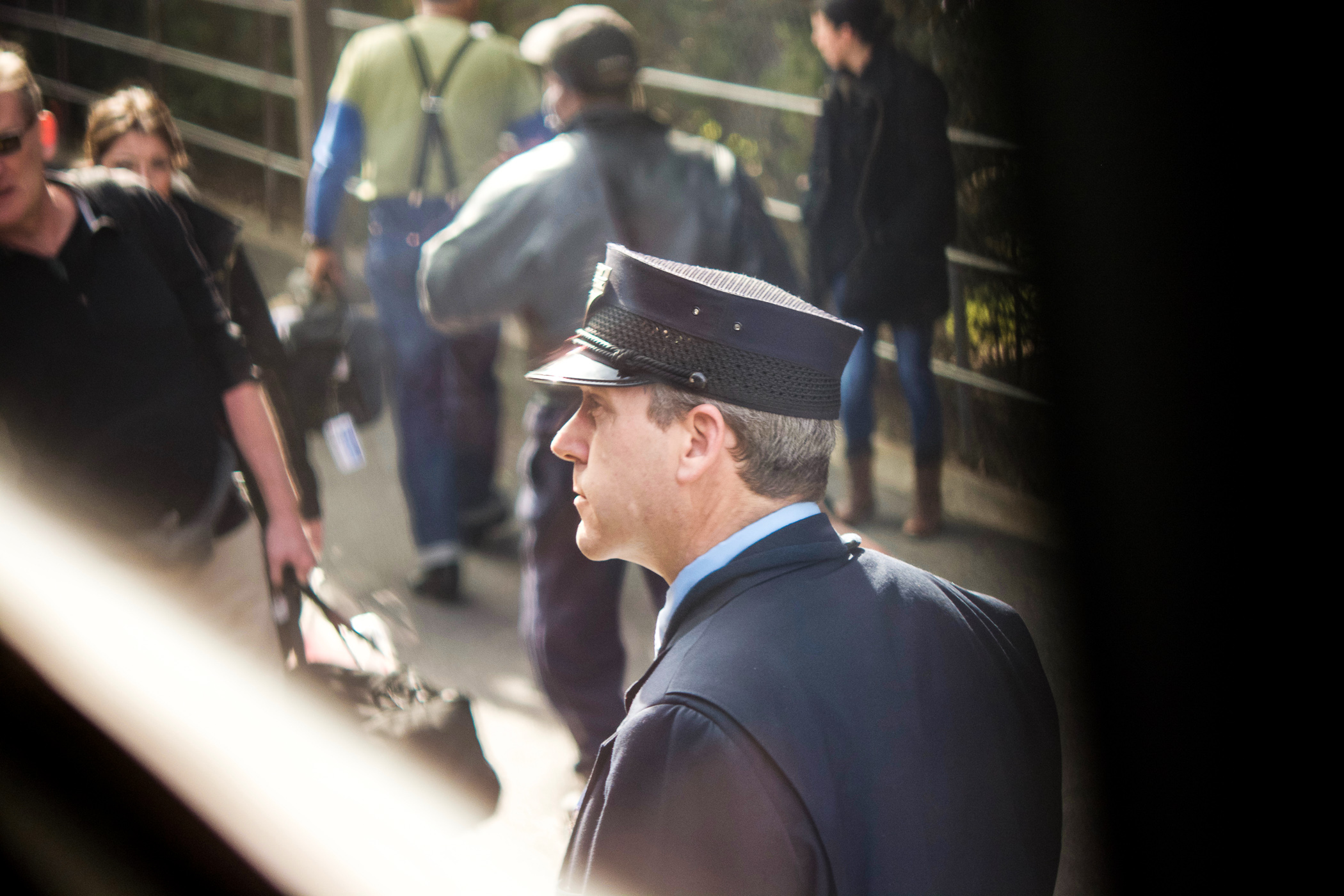 Amtrak conductor assisting passengers boarding train at Durham station.