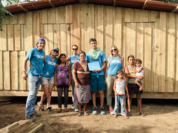 Photo Above: Our team builders (Michelle Booso with CRAD and Allie Lewbel)and family in front of their new home.