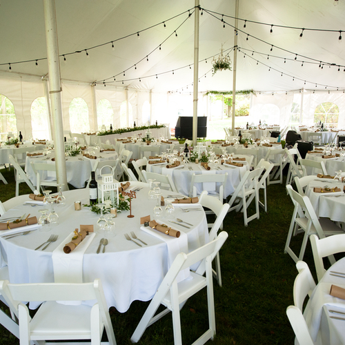 The inside of the reception tent set up with white linens, lanterns and bistro lights