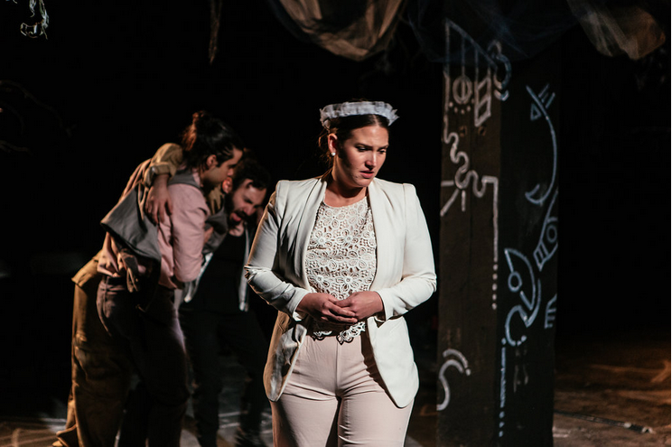 This feminine-focused and dream-like production of MacBeth had a unique visual vocabulary. Mesh, satin, and light colors stood as symbols of wealth and high-status. Here Queen Duncan wears all white and pink with a crown of white tulle. Photo by Jenny Catlow.