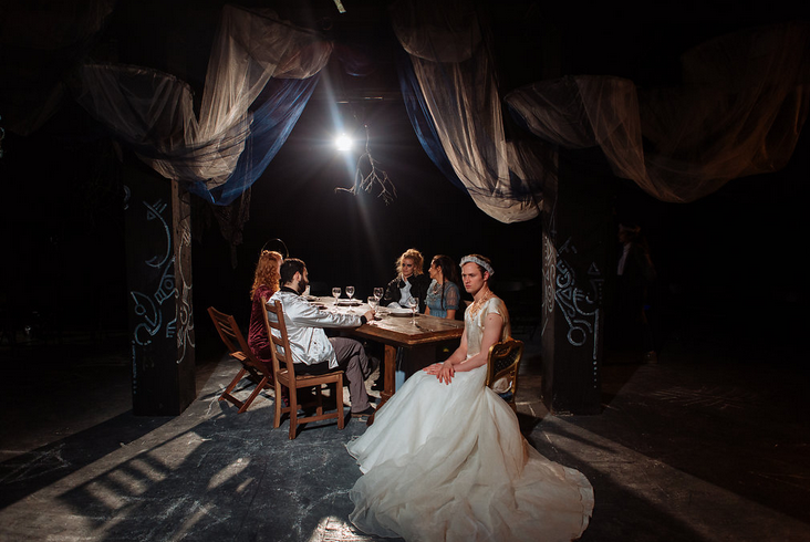 "After Lady MacBeth calls on the spirits to ""unsex her"" this production had the actors playing MacBeth and Lady MacBeth switch roles. Here you can see a masculine-bodied Queen Lady MacBeth at the banquet table. Photo by Jenny Catlow."