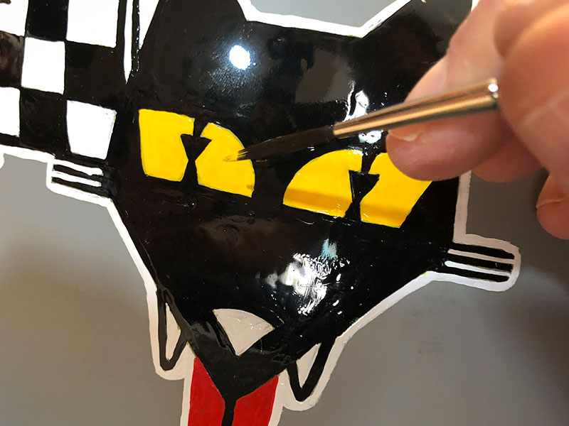 "While the sculpture was drying, I was painting the ""wolfy"" details on the helmet. Each design was based on real racing logos, except changed to show a wolf theme (Wulf racing, Carnivore spark plugs, Lupine stereo, etc.)"