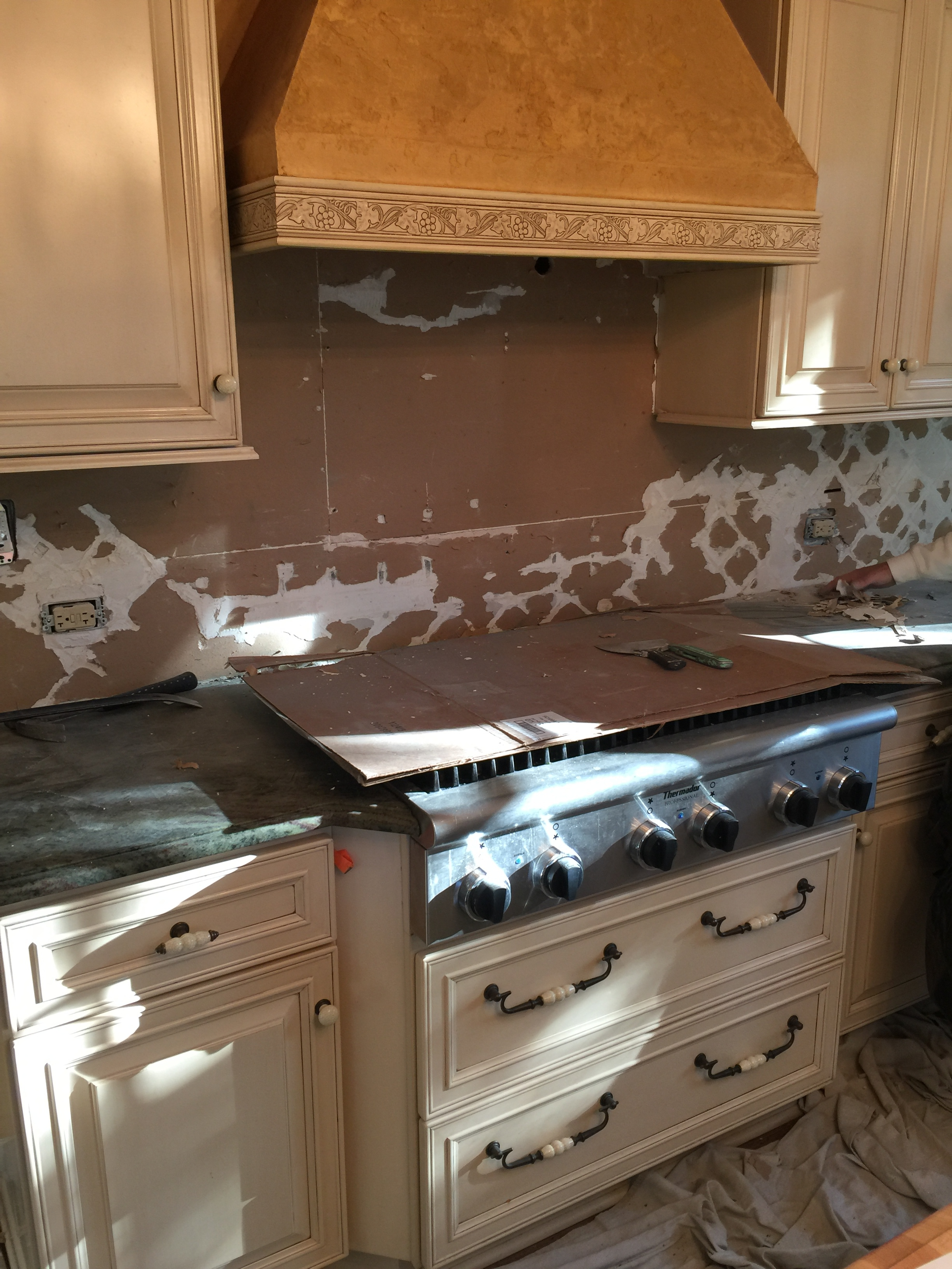 We removed the pastoral backsplash, cabinet hardware, and countertops. The china cabinet found a new home, and the walls were skim-coated smooth for paint. Cream colored cabinets were targeted for new paint. What to do about the heavily textured mustard-colored range hood?