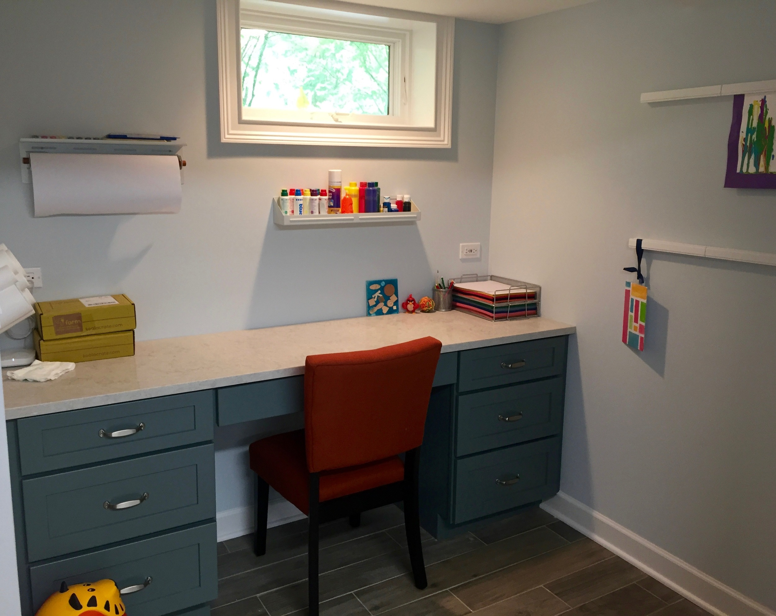A desk with a quartz top offers storage and durability to resist paint, markers, and glue. Wall-mounted organizers keep art supplies contained above the work surface. Dual outlets with 4 USB ports accommodate electronic devices and, in the future, the space can be converted to a homework station.