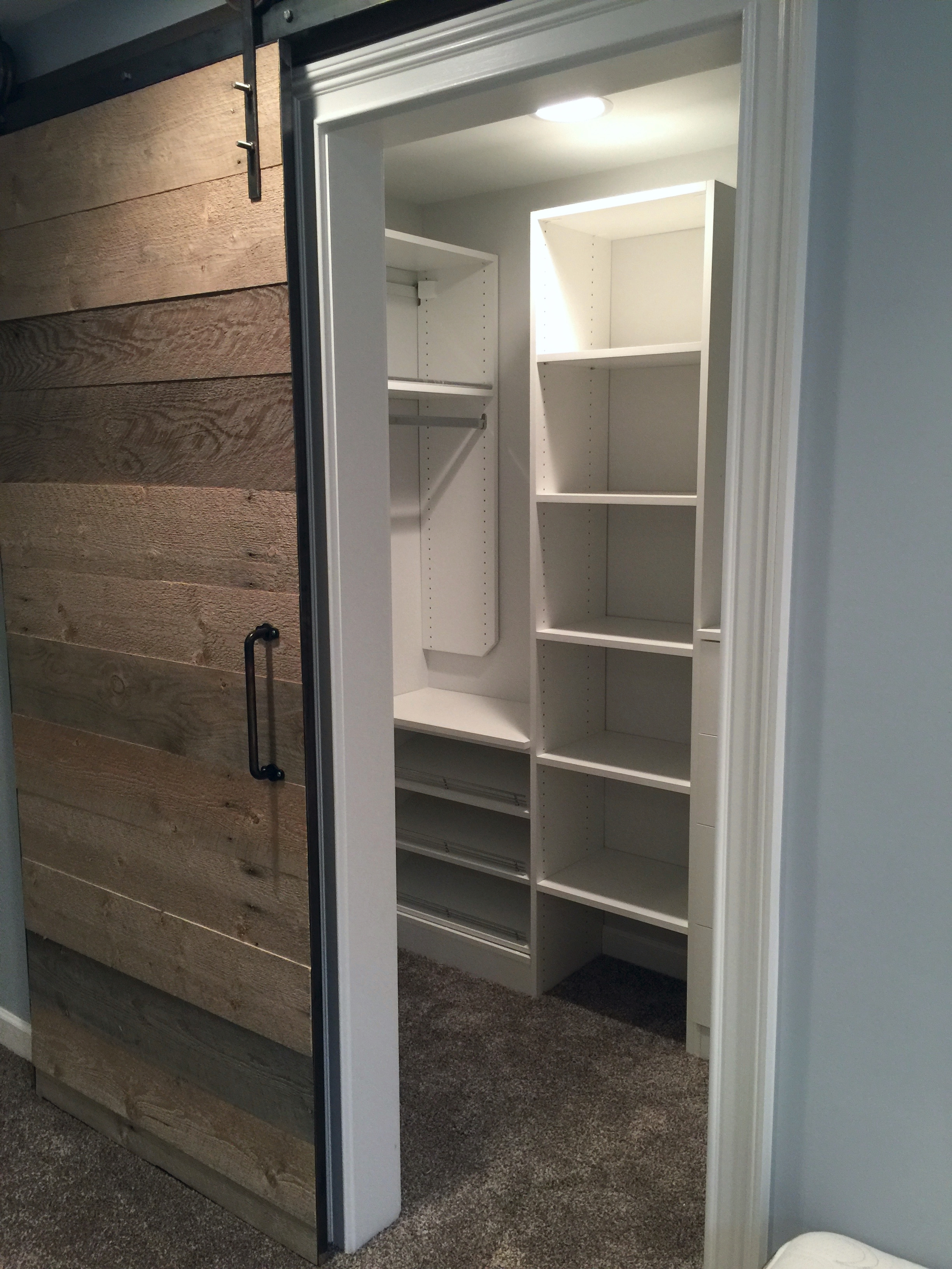 The basement bedroom closets are accessed by custom barn doors made in Utah.