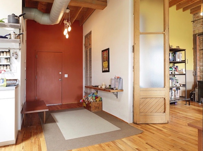 The original entry to the unit. Original wood floors, tall ceilings and passageways, and exposed ductwork are typical of the old Chicago loft conversions.