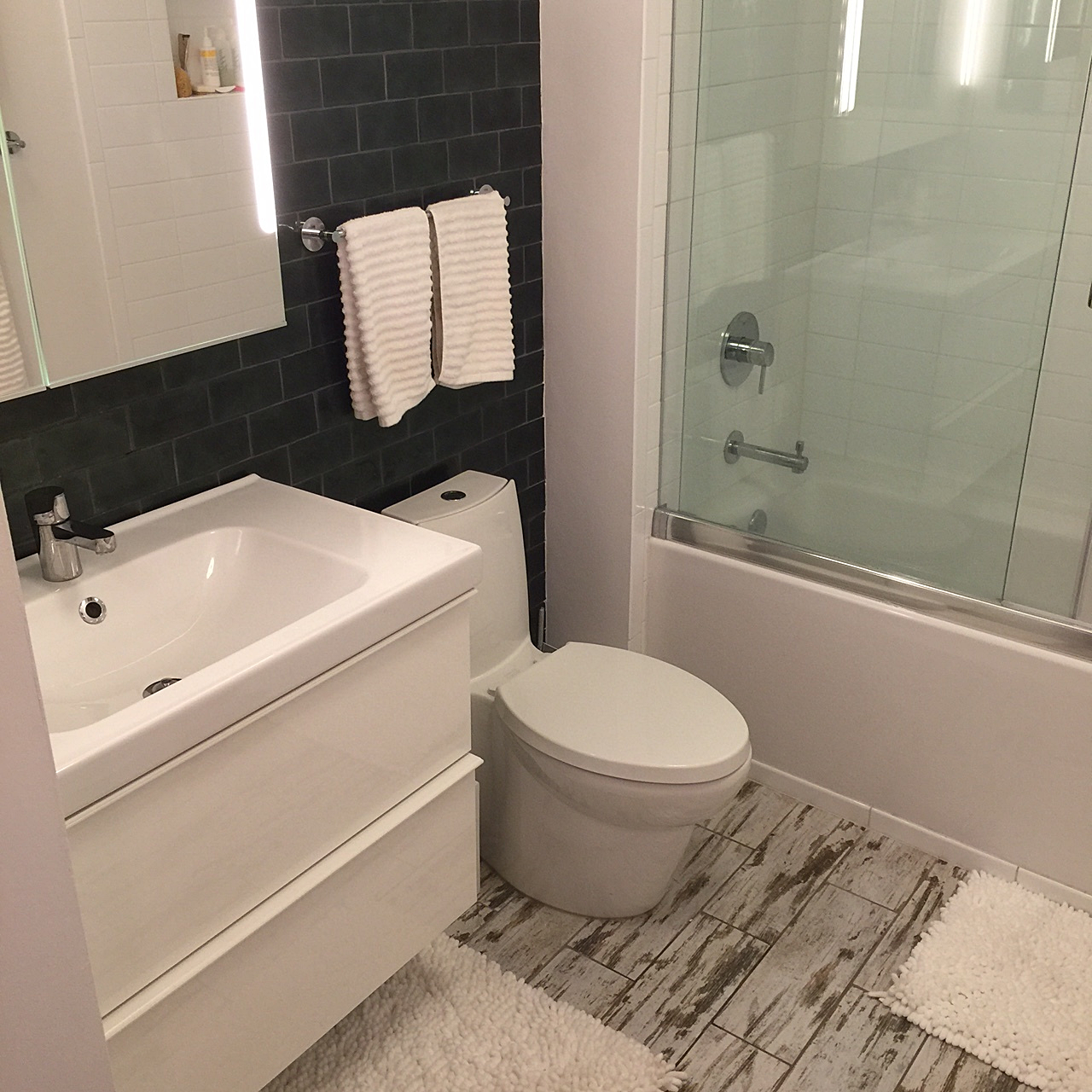 A new wall-mounted vanity, tile, lighting, and plumbing fixtures modernize the bathroom