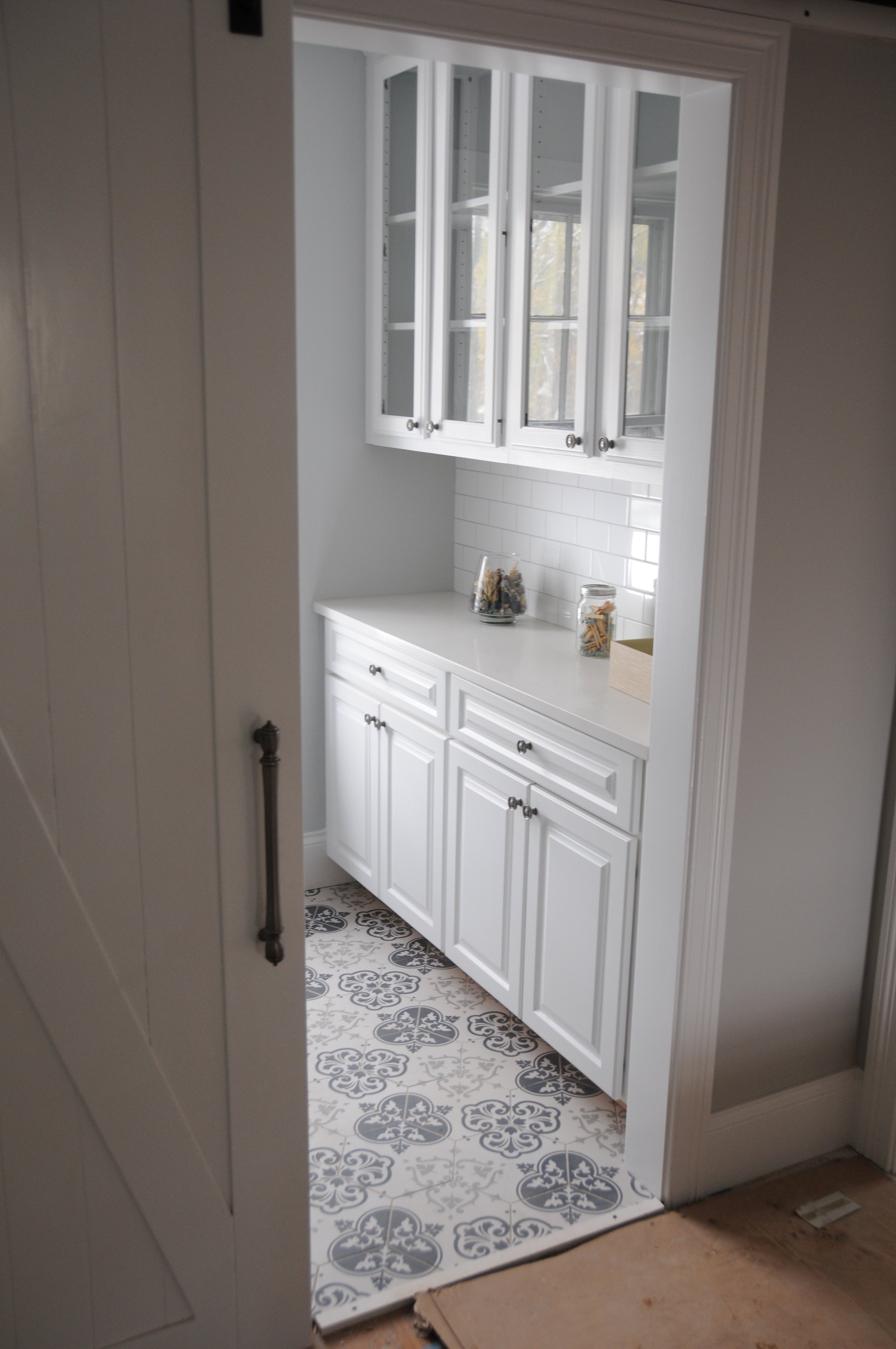 Lower and upper cabinets with a durable quartz top help make this compact laundry room punch above its weight class with regard to elegant storage. Yet another generous client donated the glass door cabinets, and repurposing them here was better than sending them to the landfill.