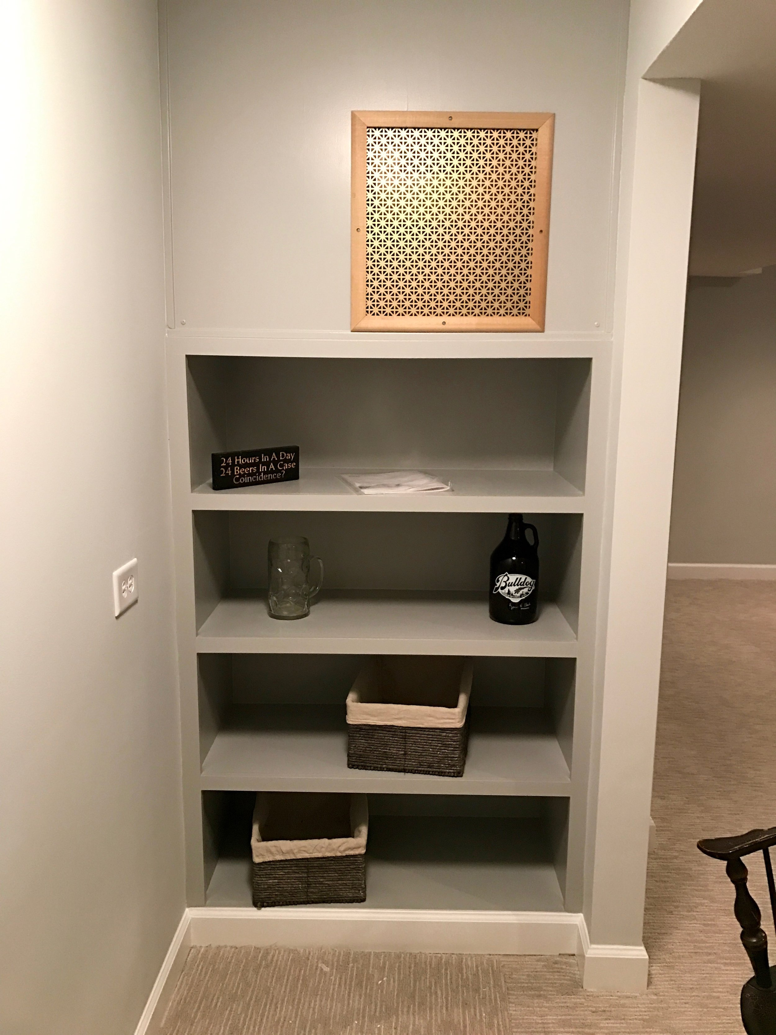 One design problem with wine cooling units is that they often project out of the wall much like a window-mounted air-conditioner. In this instance, we built a custom shelving unit with a grill to allow for additional storage, air transfer, and better visuals. Removable panels allow for easy access to the wine cooling unit if it needs service.