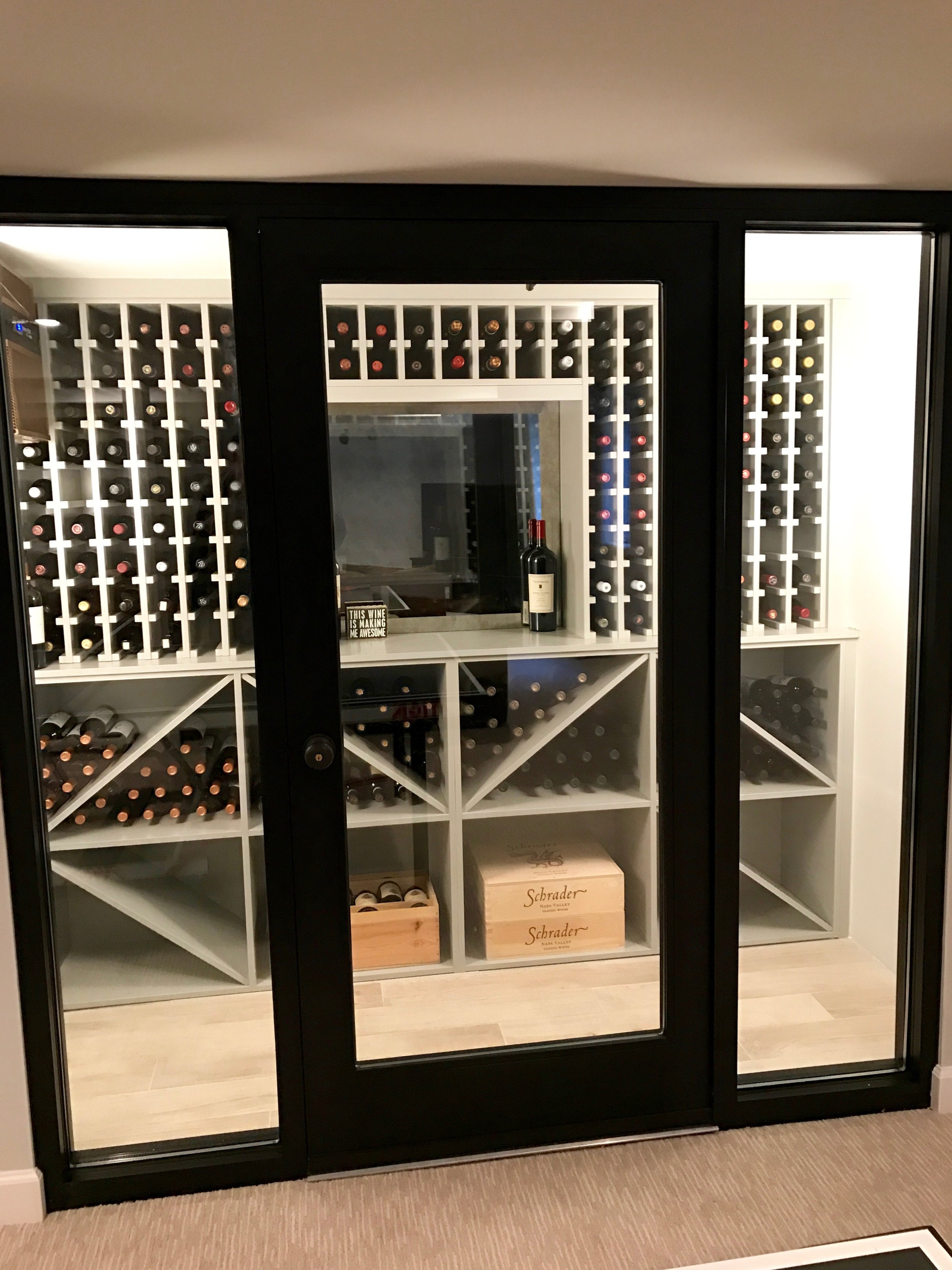 This wine cellar was created to hold hundreds of bottles in different formats behind insulated glass and a special door with a thermal break in the frame to maintain 55 degrees fahrenheit and controlled humidity. T he walls and ceiling are fully insulated to help the cooling unit operate efficiently. The custom wine storage unit is a modernized take on the traditional dark wood cabinetry.