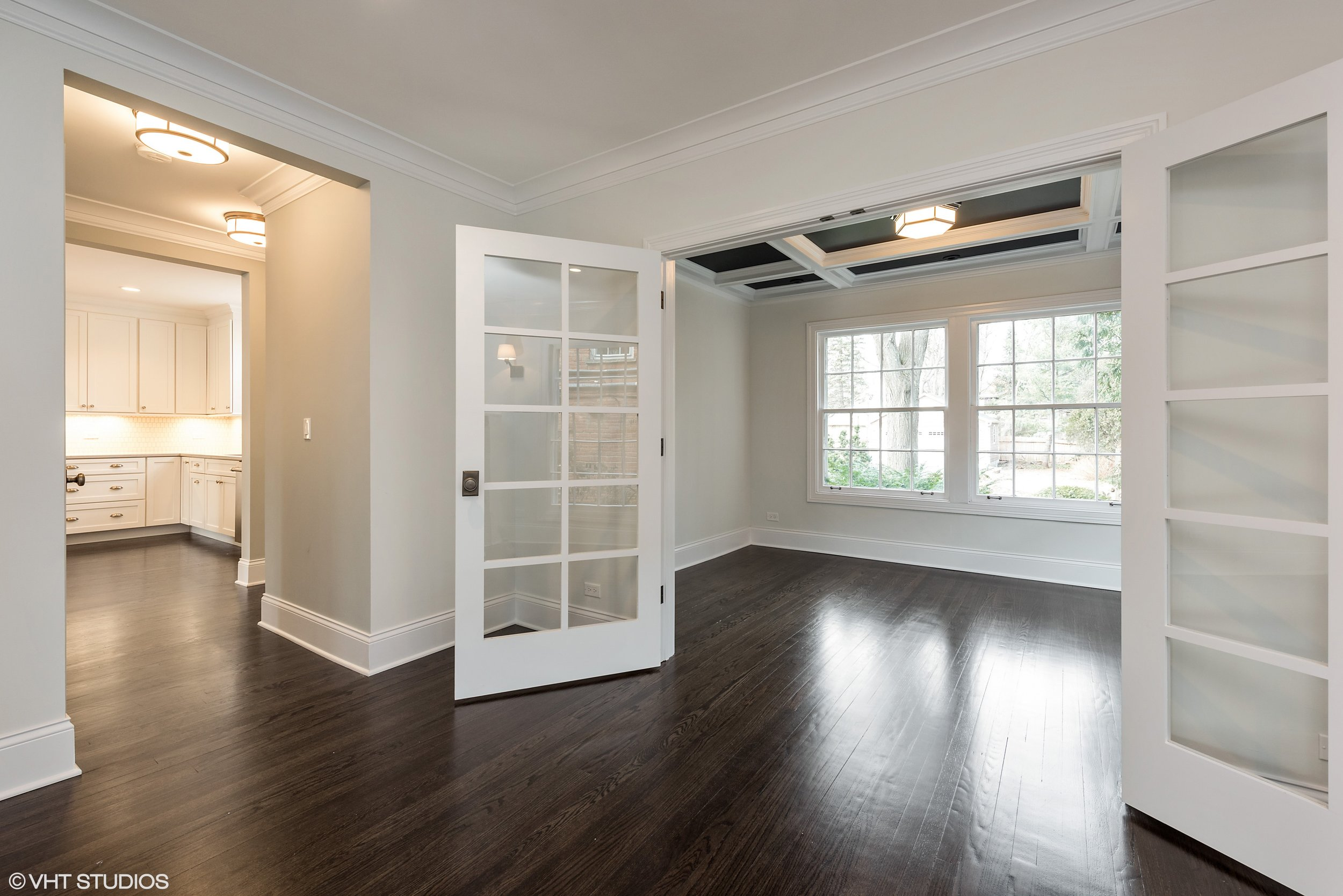 "One way to reduce the ""bowling alley"" effect of the large colonial living room is to create some visual separation. In this example, we added french doors and a coffered ceiling to separate the study from the living room. We also added a passage to the kitchen to improve the flow of the house."