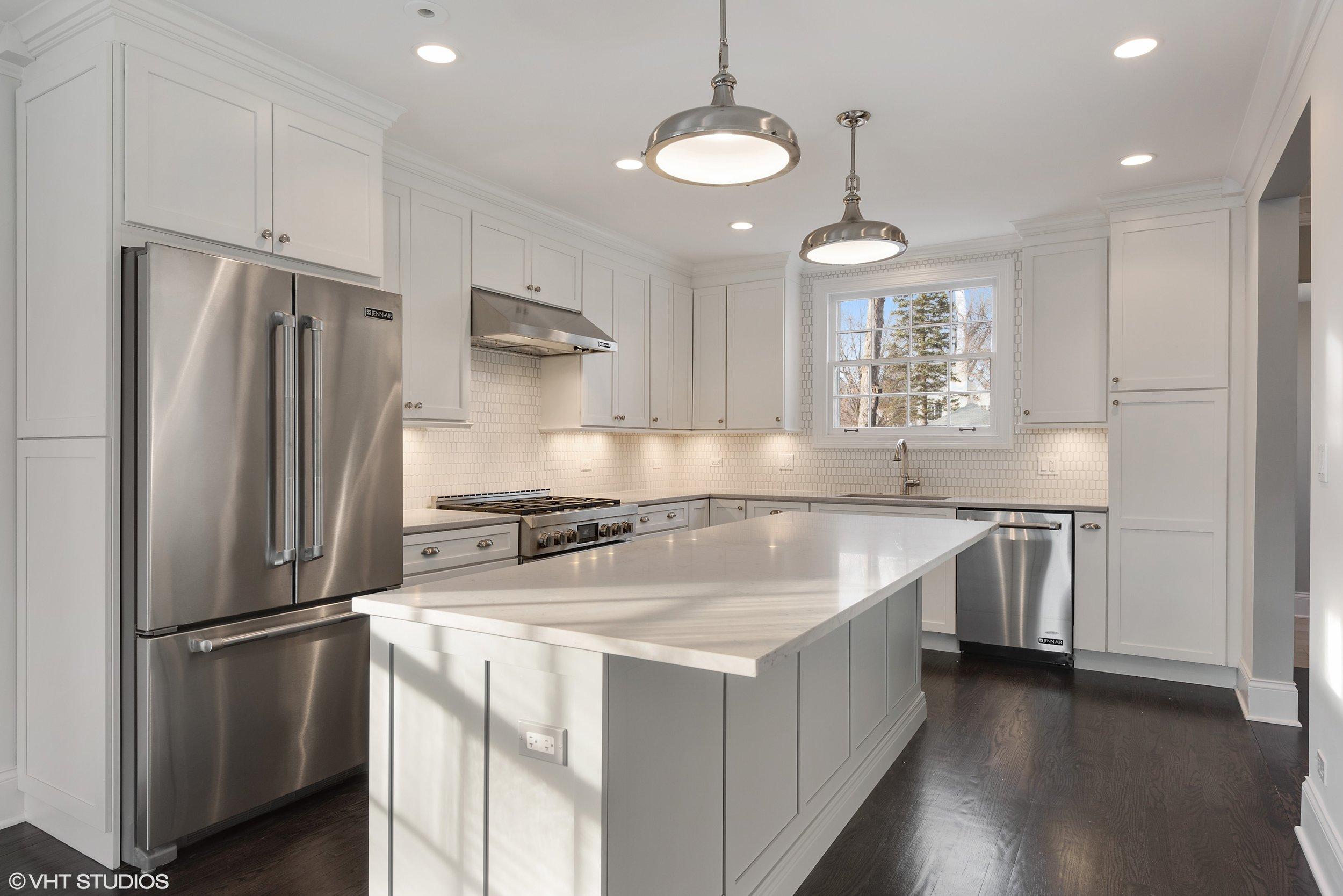 The kitchen was a prime example of adapting the layout to today's family: small, dark and closed off by a wall where the refrigerator is now, the new kitchen benefitted from a more spacious expansion, as well as new appliances, cabinetry, and lighting.