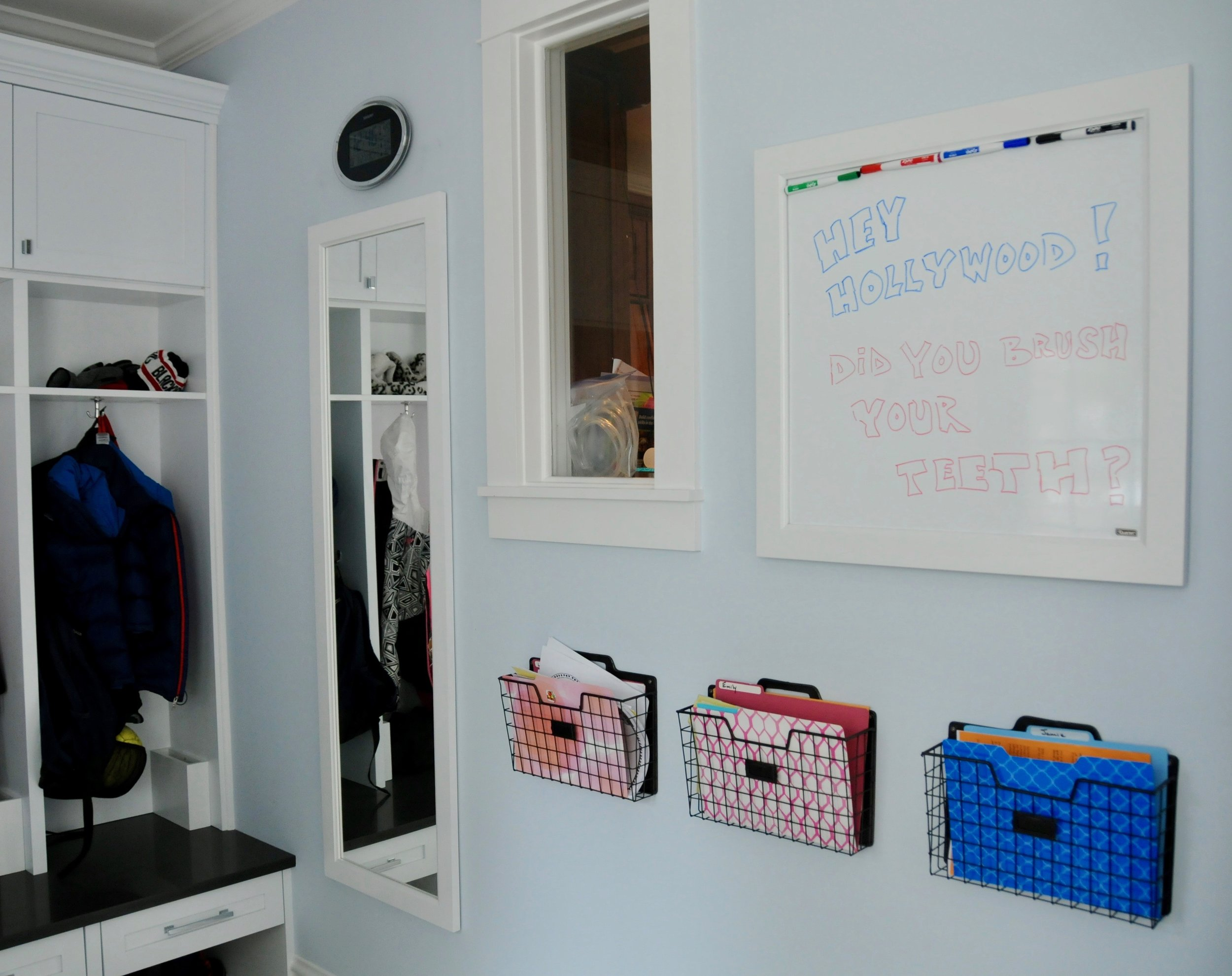 We framed the mirror and white board to match the cabinetry, each child has a school basket, and the whiteboard is a convenient messaging companion to all of the devices in our digital world.