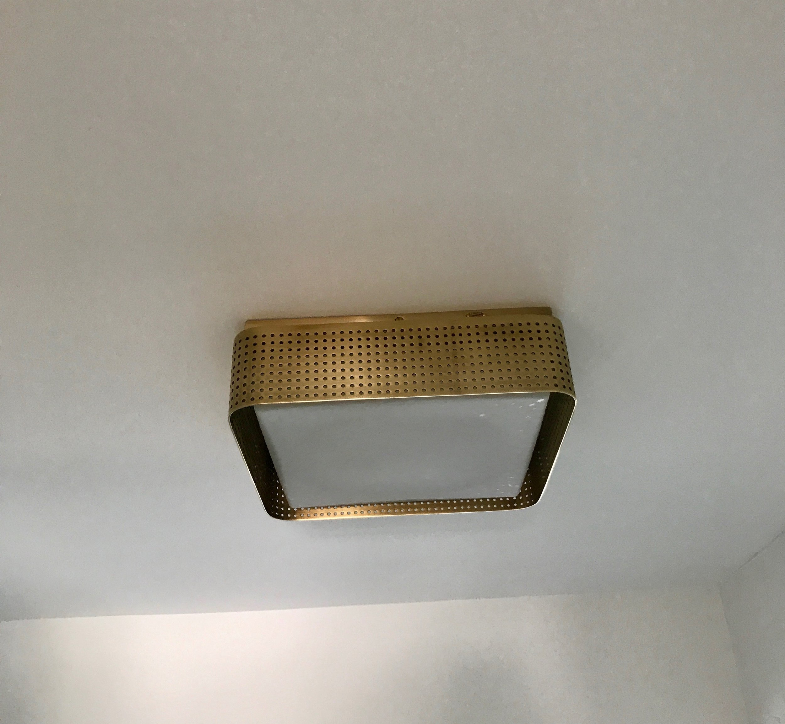 The Kelly Wearstler brass-wrapped ceiling light echoes the vanity pulls.