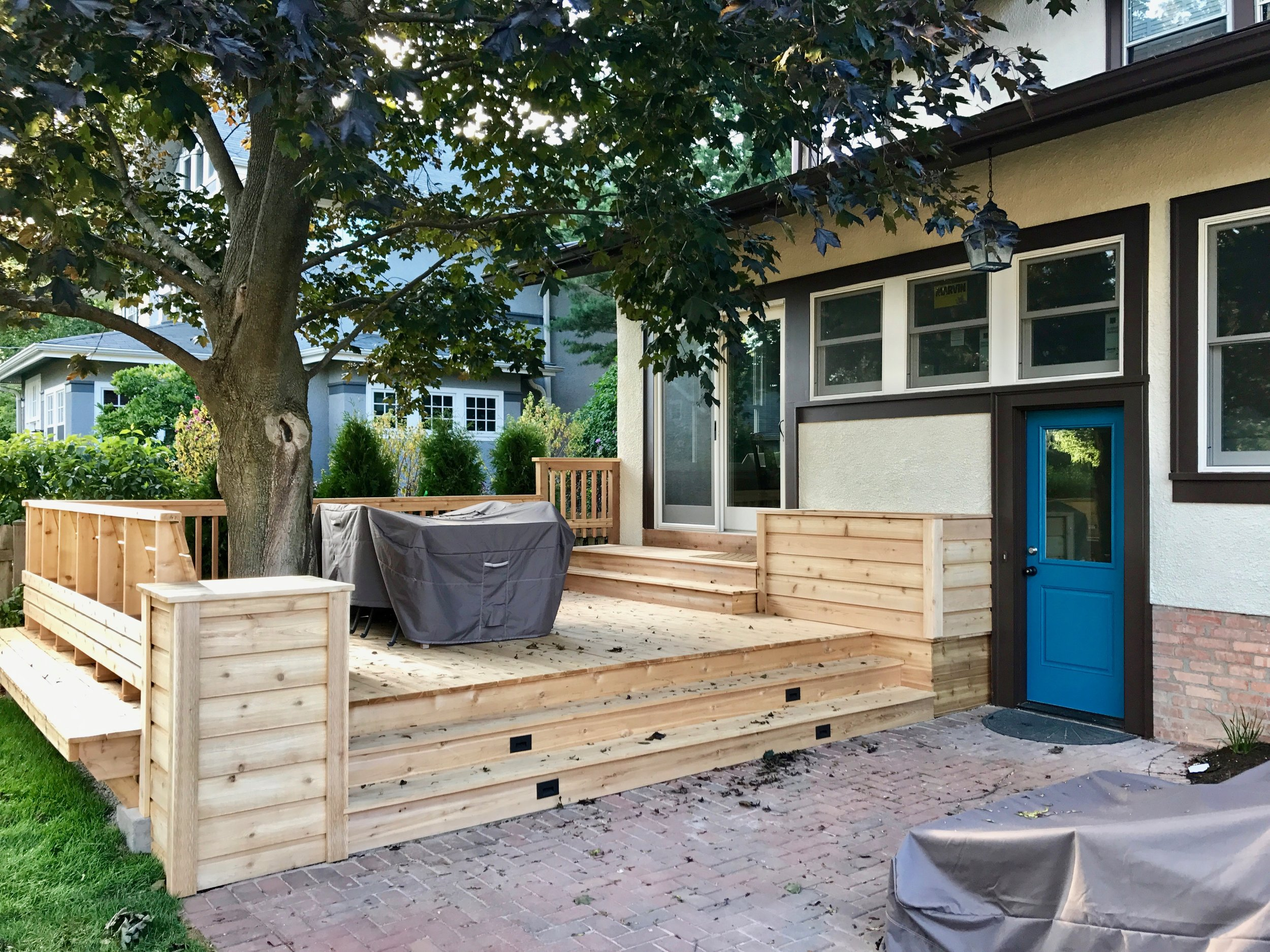 A view of the finished deck with all new MARVIN windows, planter box, pendant lighting, and door. The transformer for the deck lighting is hidden inside the planter box.