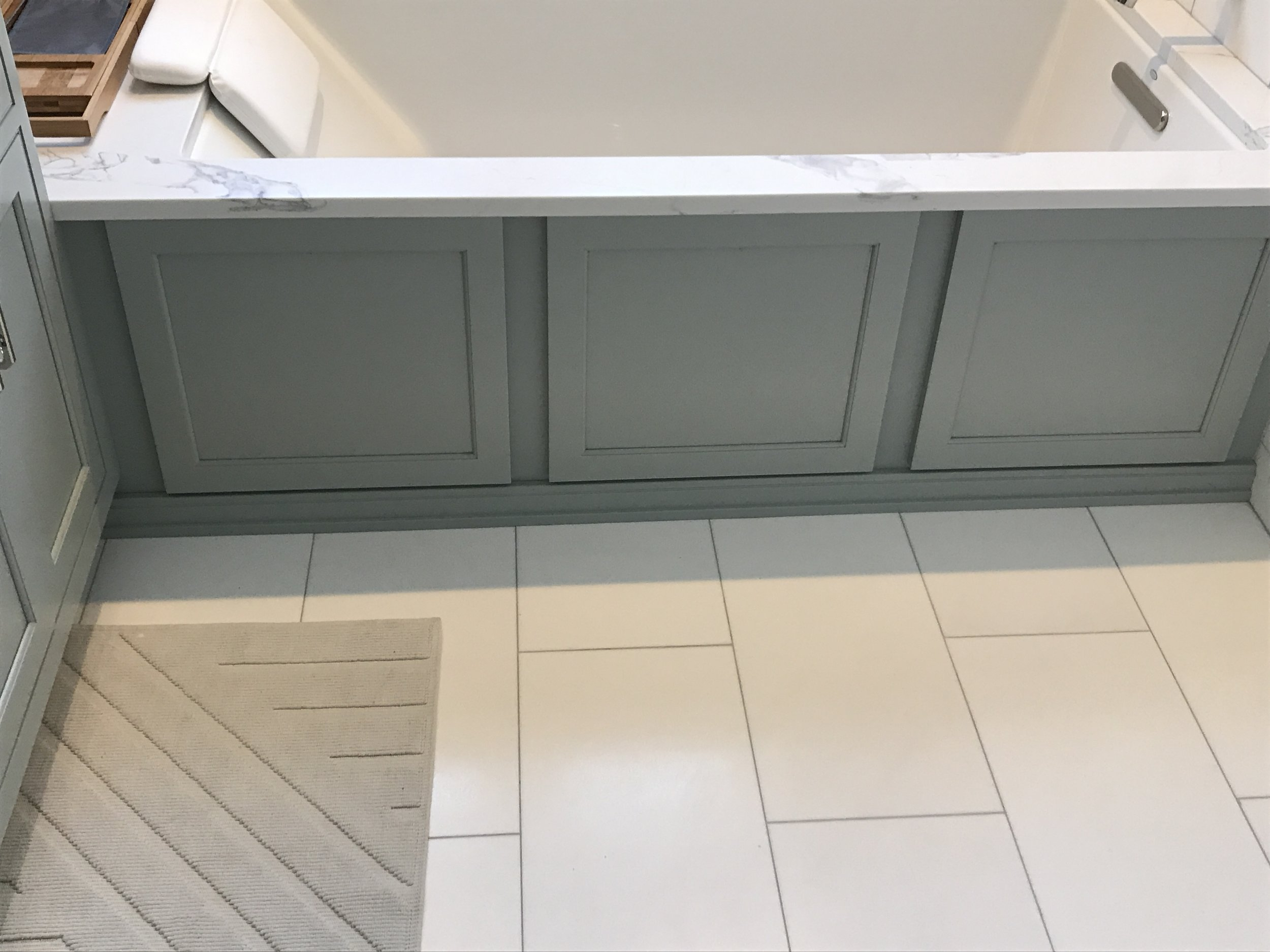Custom skirt for tub deck, color matched to the vanity and wainscot on opposite wall, and a quartz deck surround.