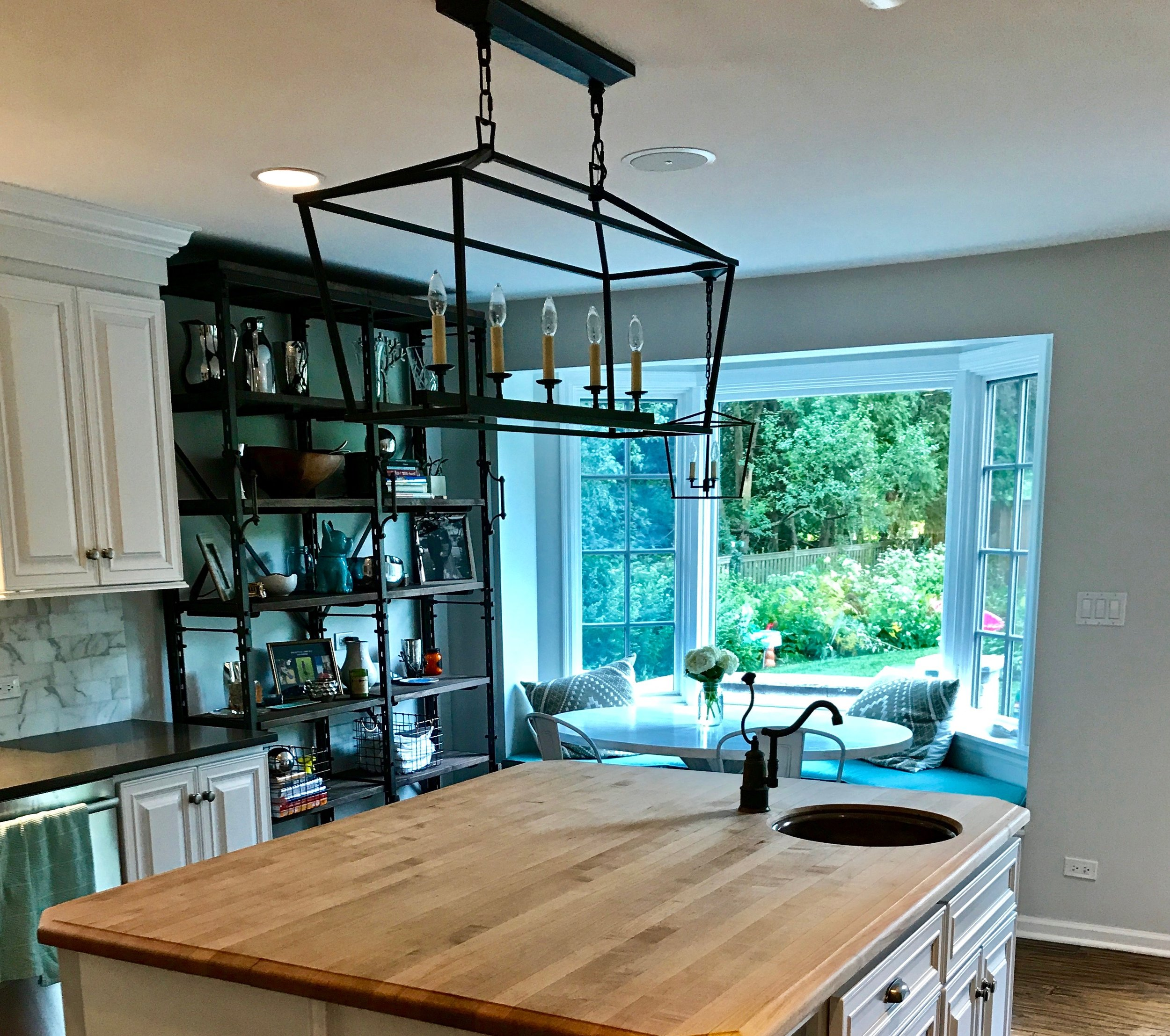 A view of the refinished island top, new light fixtures, and the shelving unit next to the bay window.