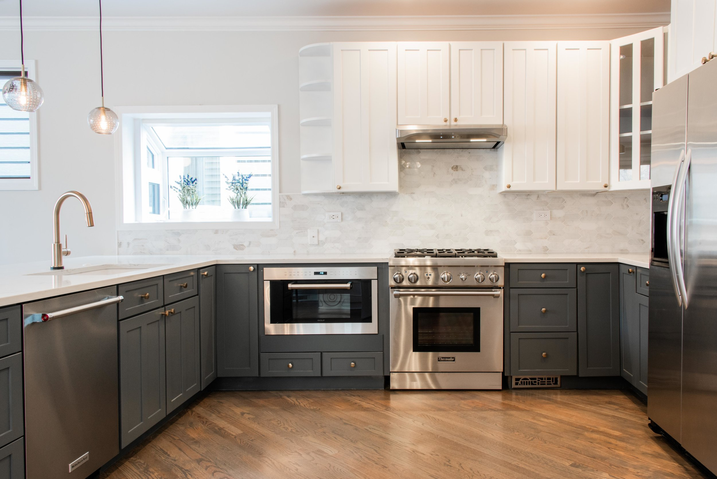 The refinished cabinets, with a new range and under-counter microwave, countertops, backsplash and lighting.