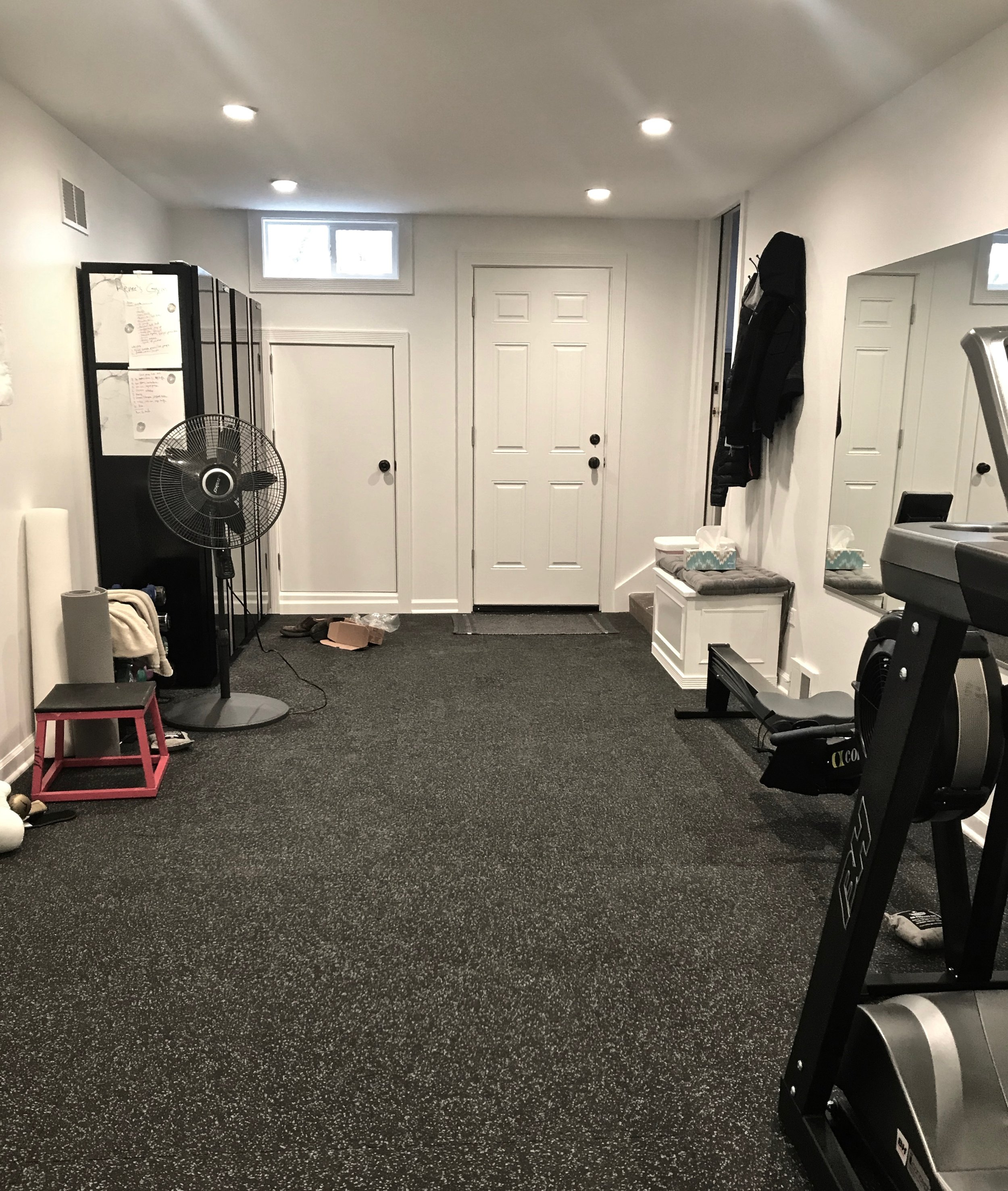 A view of the entry to the gym, with closed storage, new exterior door, new windows, and lockers. The clients can check their form in the 6' x 4' wall mirror, too. Heat is drawn from the main ductwork inside the home, and the walls are coated in a special scuff-resistant paint.