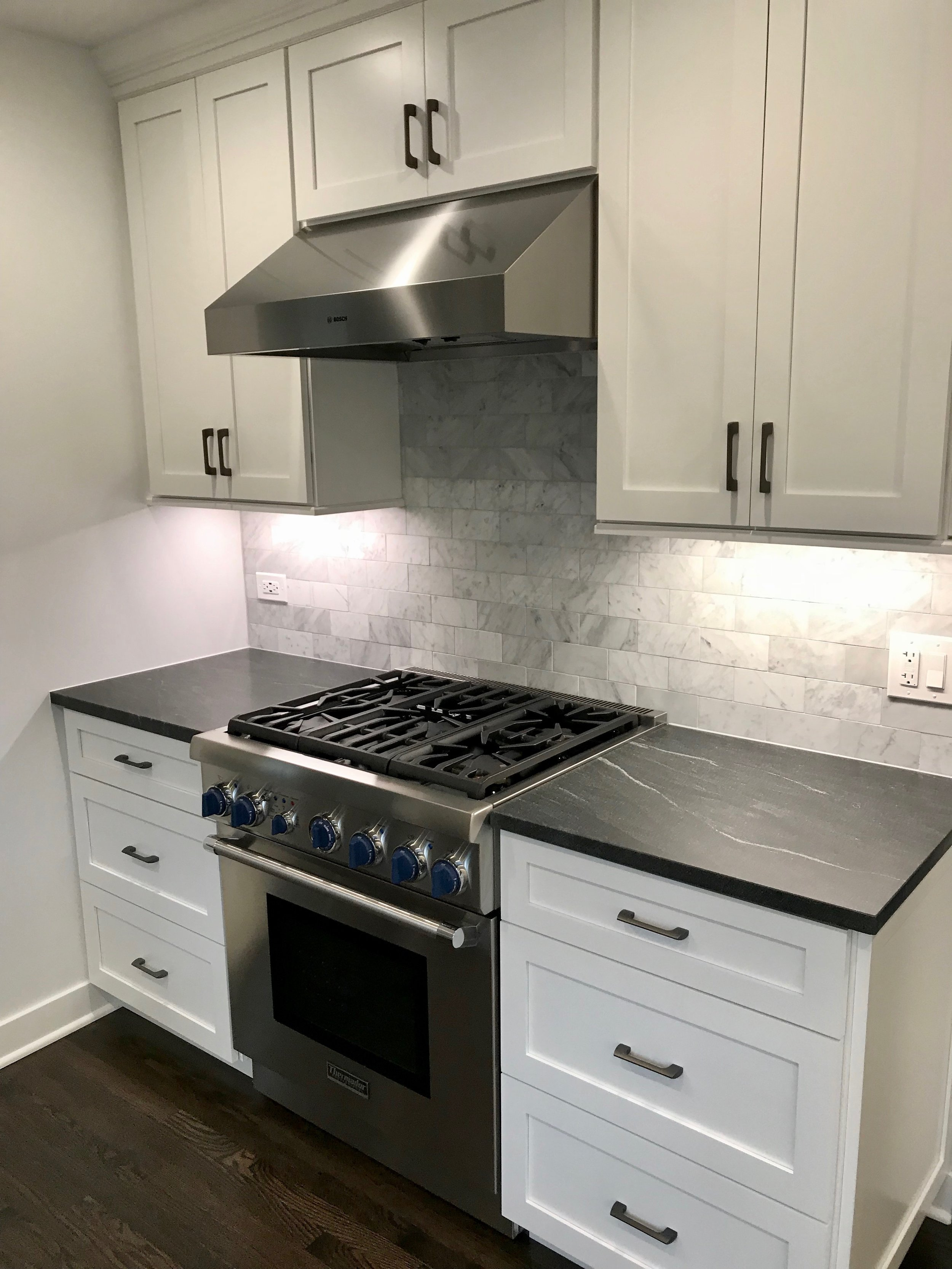 Semi-custom or custom cabinetry is a good choice for many kitchens.It allowed us to center the range on the wall and add valuable storage and prep space on both sides.