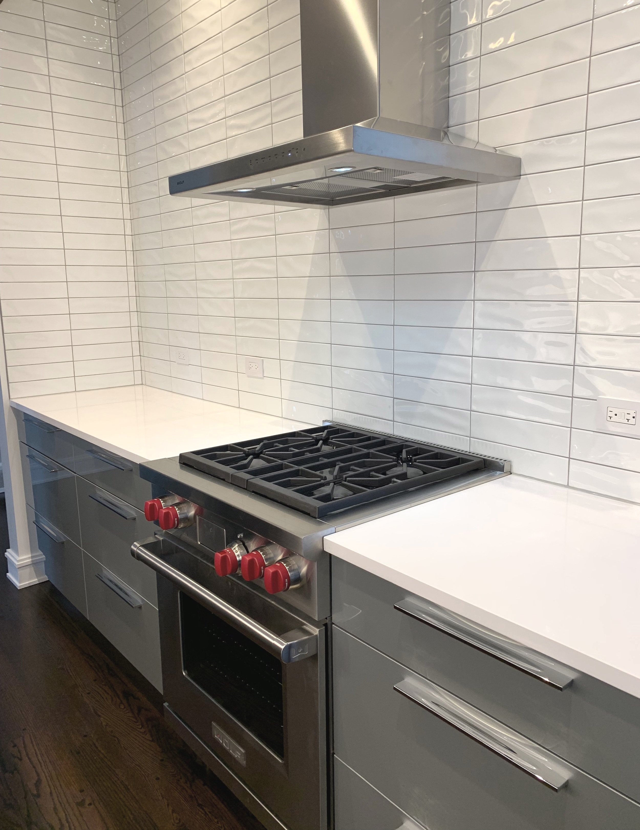 A view of the Wolf dual-fuel range and backsplash to the ceiling with undulated tile. No upper cabinets clutter the space. Generous organized storage under the counter was sufficient for these clients.