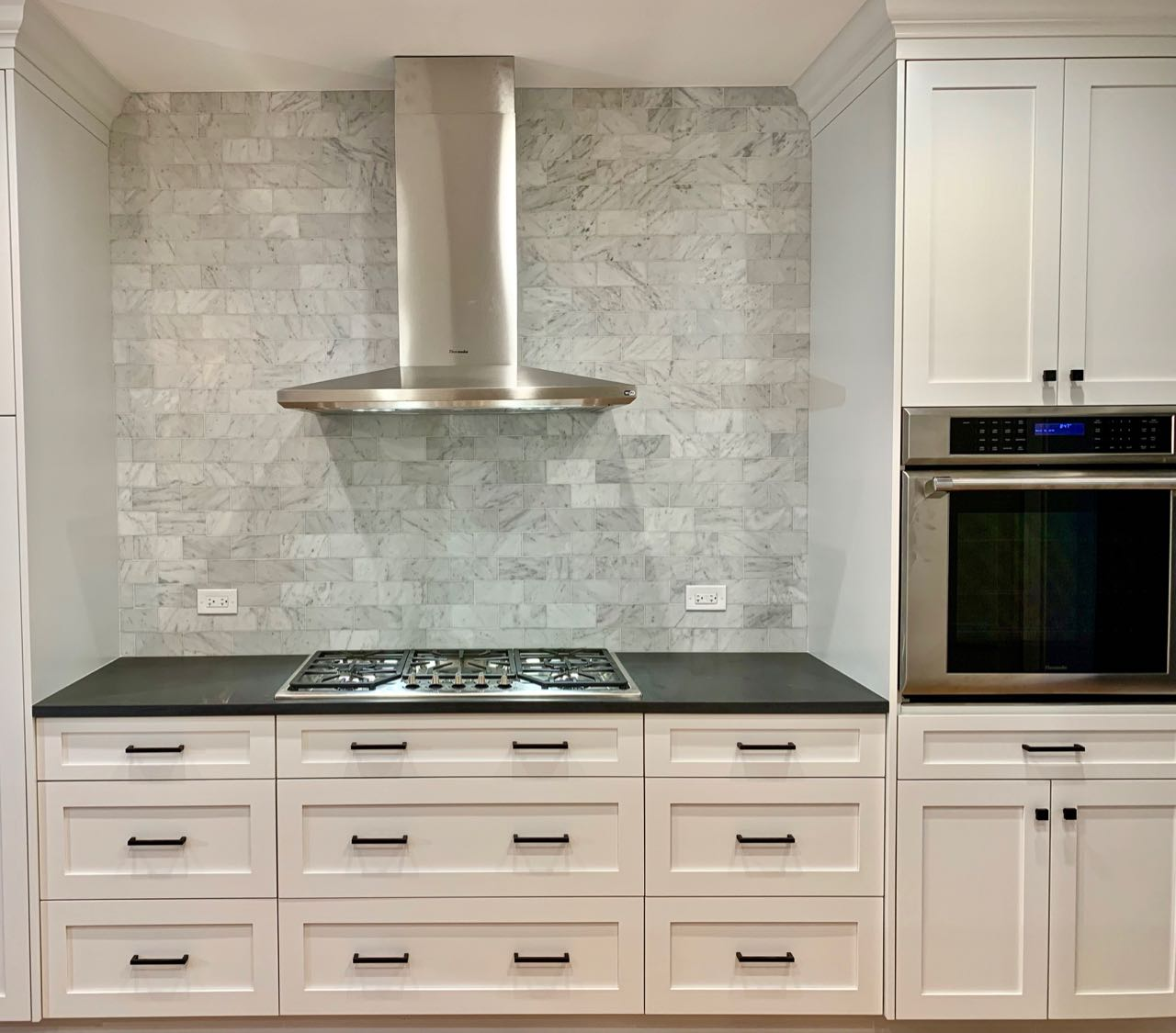 A view of the cooktop wall. Drawers are preferable to doors in this location for convenient access to pots, pans, and cooking utensils. Although there was enough space for one more wall cabinet on either side of the hood vent, it would have added visual clutter without adding much usable storage.