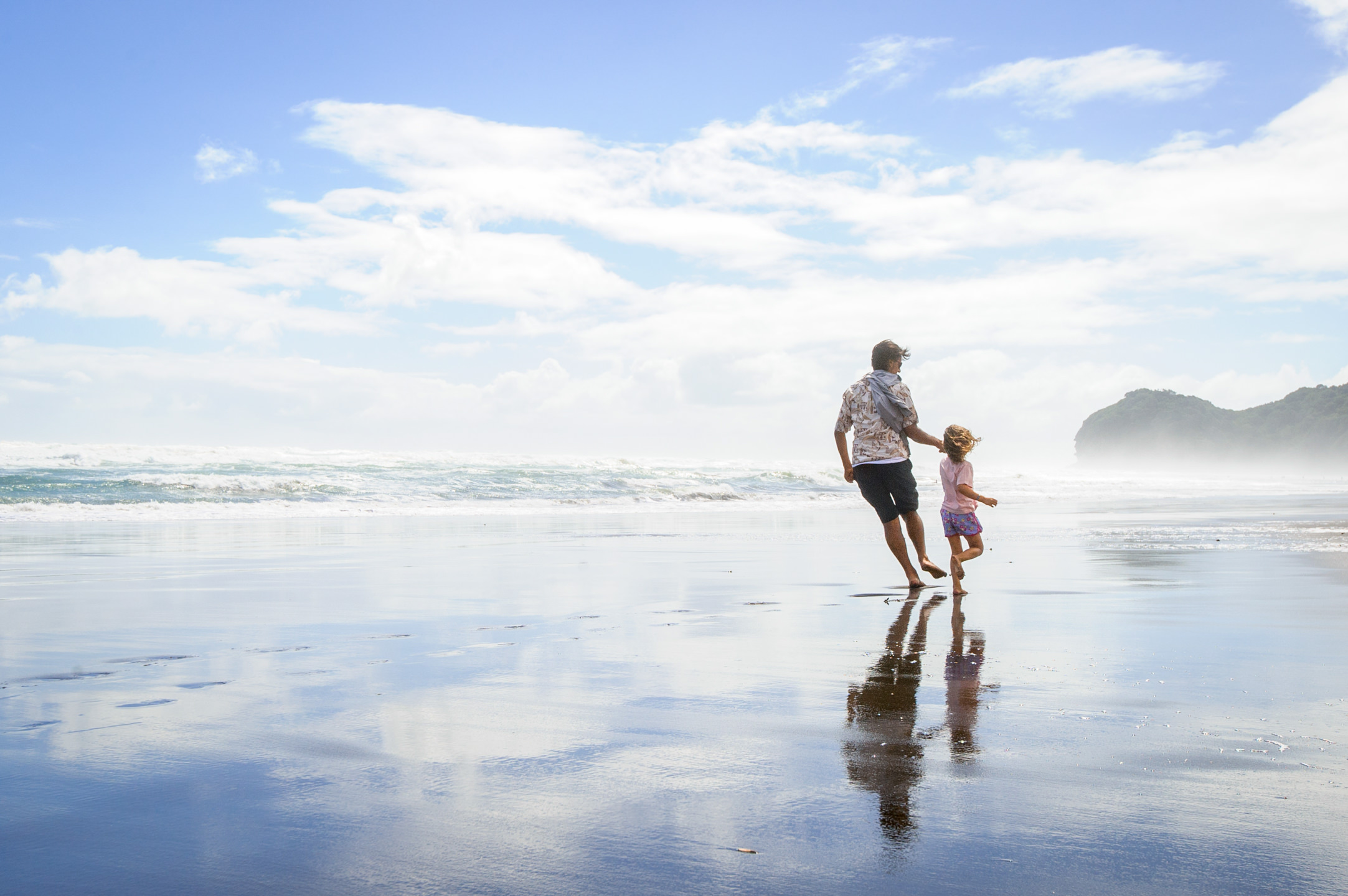 A father and daughter run along Piha Beach on the west coast of North Island New Zealand